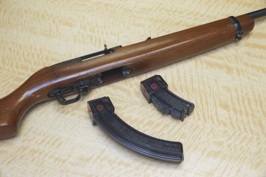 A semi-automatic rifle is displayed with a 25 shot magazine (left) and a 10 shot magazine (right) at a gun store in Elk Grove, California.