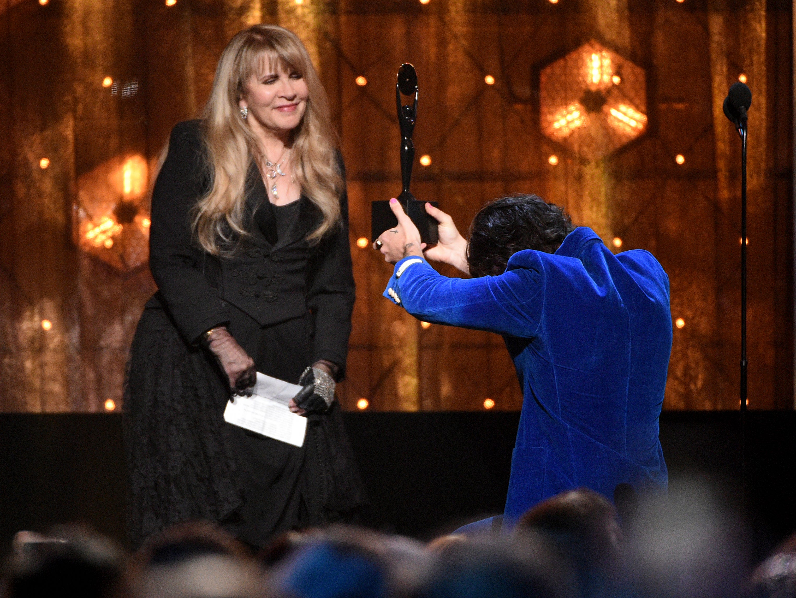 Harry Styles, right, presents a trophy to Stevie Nicks at the Rock & Roll Hall of Fame induction ceremony at the Barclays Center on Friday, March 29, 2019, in New York. (Photo by Evan Agostini/Invision/AP) ORG XMIT: NYPM150