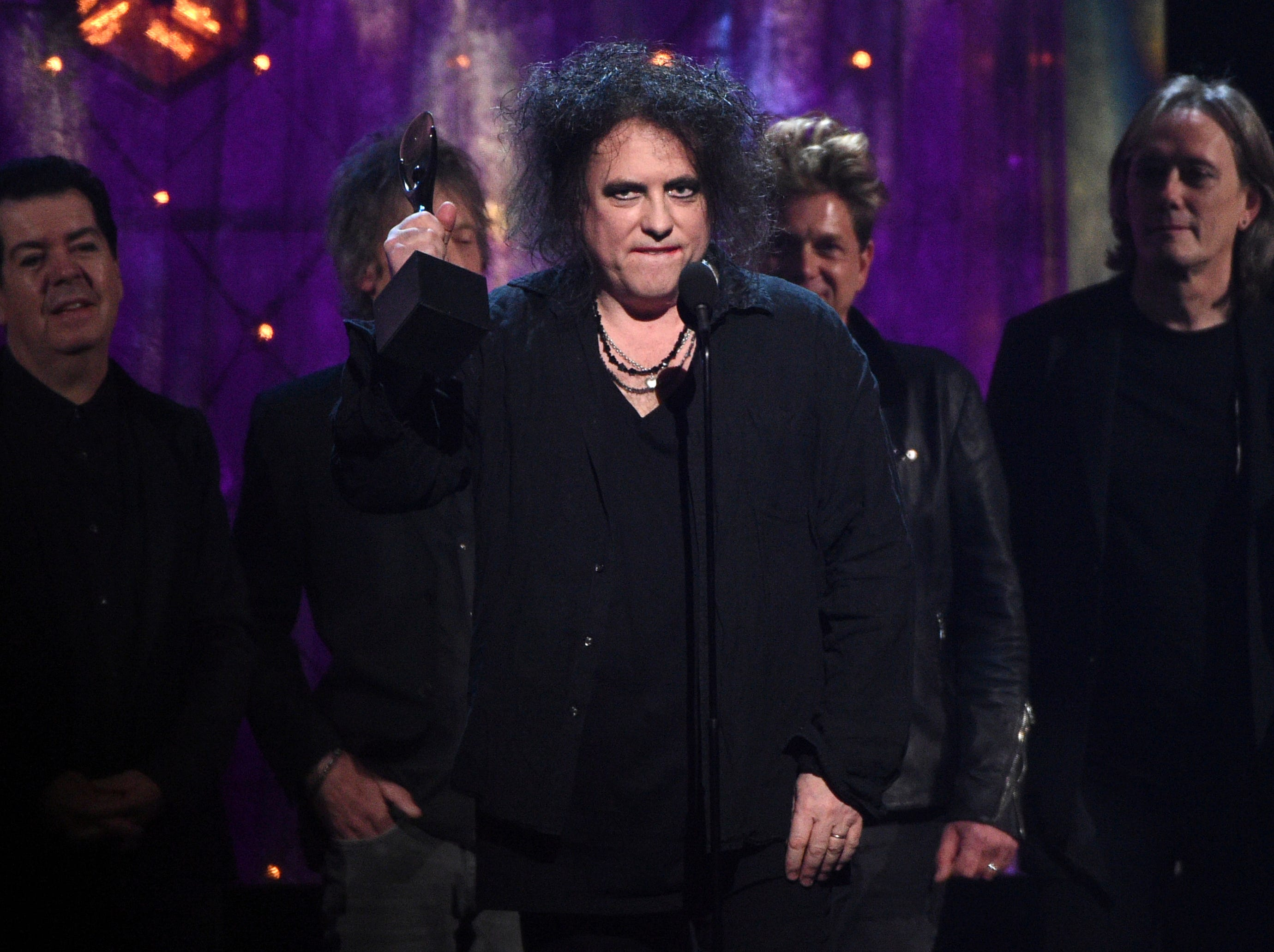 Robert Smith of The Cure accepts a trophy at the British band's induction.