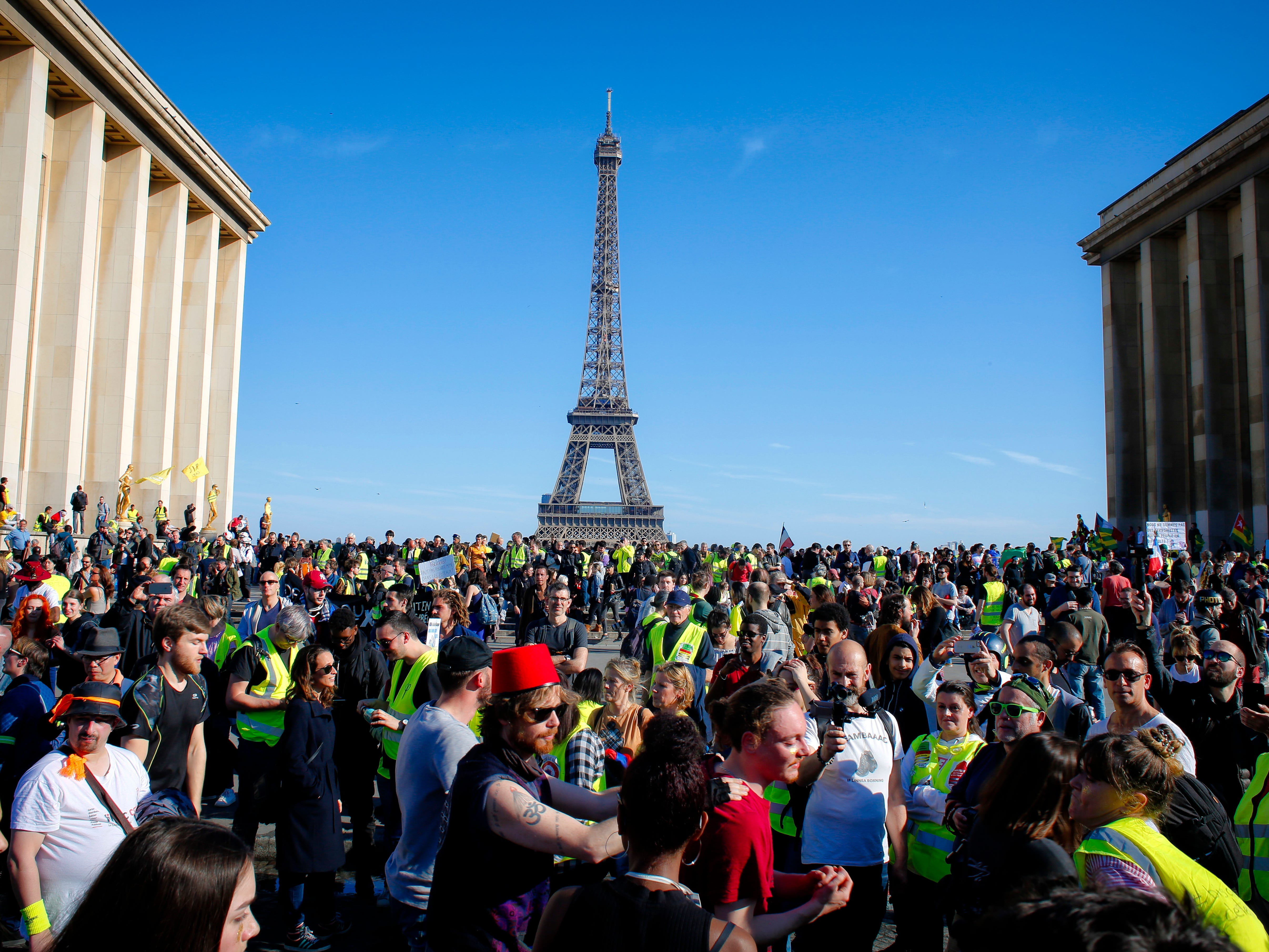 French yellow vest protesters, backdropped by the Eiffel Tower are rallying to support an older woman activist injured in a confrontation with police, Saturday, March 30, 2019 in Trocadero Square, in Paris. The demonstrators are undeterred by protest bans or repeated injuries in 20 weeks of demonstrations, marching again Saturday in Paris, Bordeaux and other cities to keep pressing President Emmanuel Macron to do more to help working classes, redesign French politics or step down altogether.