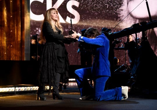 Harry Styles dramatically presents Stevie Nicks with her token from the Rock Hall.