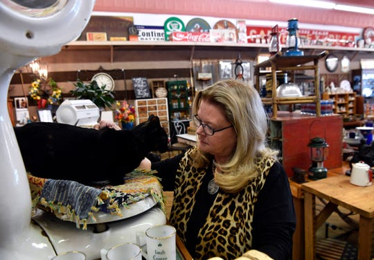 Linda Short pets her store cat Rosie at Texas Star Antiques in Haskell on March 21. Short has purchased the building at which the Anderson Book Store is closing and hopes to turn it into a county museum.