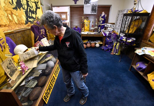 Jane Short adjusts some of the memorabilia in the Rochester Museum dedicated to the town school's sports tradition March 21. Short's daughter-in-law Linda hopes to start a similar museum in Haskell.