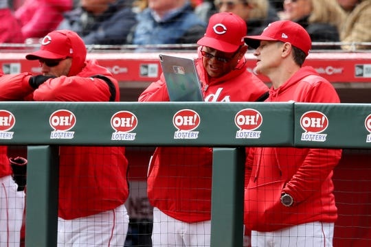 Cincinnati Reds bench coach Freddie Benavides (45) and Cincinnati Reds manager David Bell (25) look over a document in the first inning of an MLB baseball game against the Pittsburgh Pirates, Sunday, March 31, 2019, at Great American Ball Park in Cincinnati.