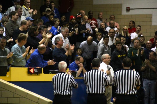 Taken in January 2013 in a Covington Catholic win over Newport Central Catholic, basketball fans applaud Jack Kaelin, who was honored for 50 years as a CovCath teacher. Kaelin has his hands folded between the first two officials from the left.