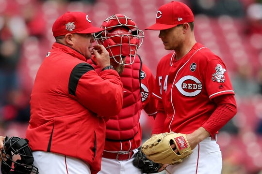 Cincinnati Reds pitching coach Derek Johnson (36) talks to Cincinnati Reds starting pitcher Sonny Gray (54) on the mound in the second inning of an MLB baseball game against the Pittsburgh Pirates, Sunday, March 31, 2019, at Great American Ball Park in Cincinnati.