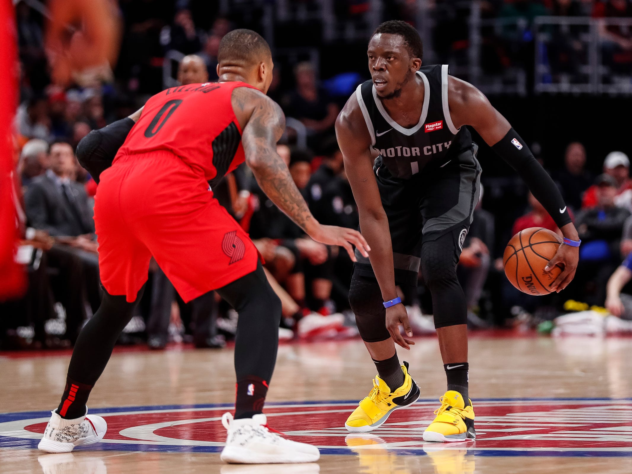Reggie Jackson dribbles against Portland Trail Blazers guard Damian Lillard during the second half of the Detroit Pistons' 99-90 win Saturday, March 30, 2019, at Little Caesars Arena.