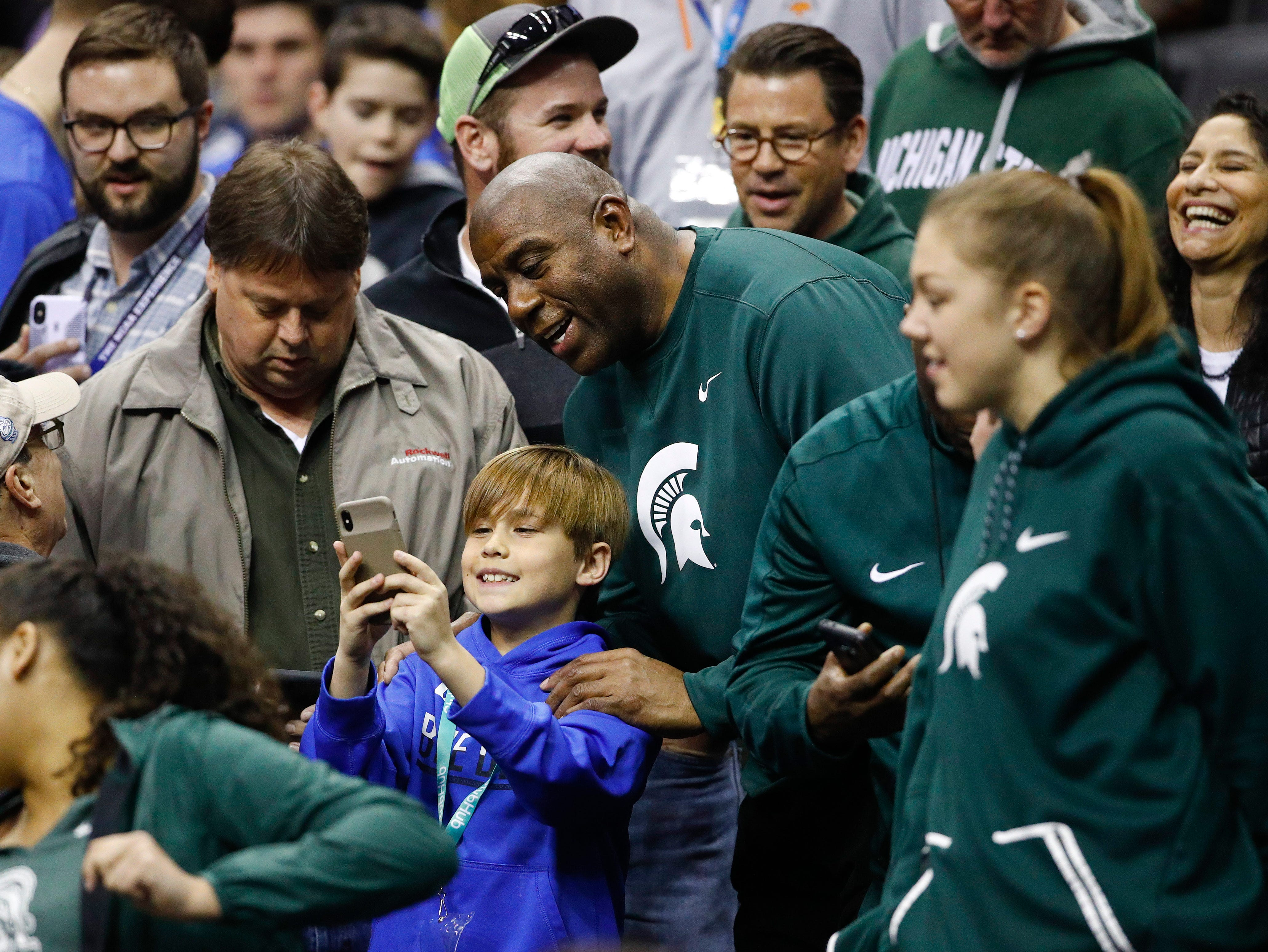 Los Angeles Lakers president and Michigan State alumnus Magic Johnson, center, poses for photos before an NCAA men's East Regional final college basketball game between Michigan State and Duke in Washington, Sunday, March 31, 2019. (AP Photo/Patrick Semansky)