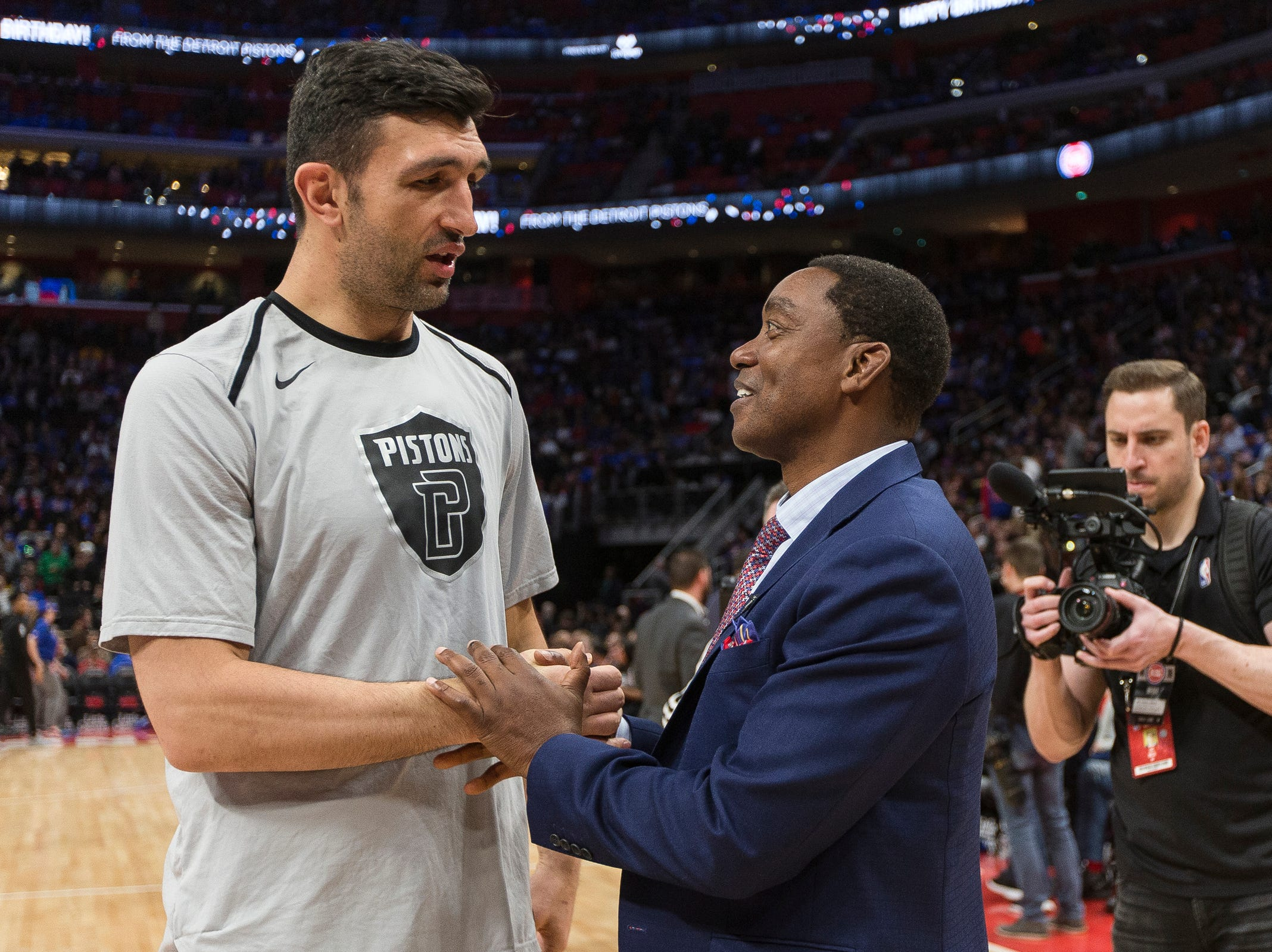 Isiah Thomas talks to center Zaza Pachulia during the celebration for the Bad Boys' 30th anniversary of the 1989-90 back-to-back championships during the Pistons' 99-90 win over the Trail Blazers on Saturday, March 30, 2019, at Little Caesars Arena.