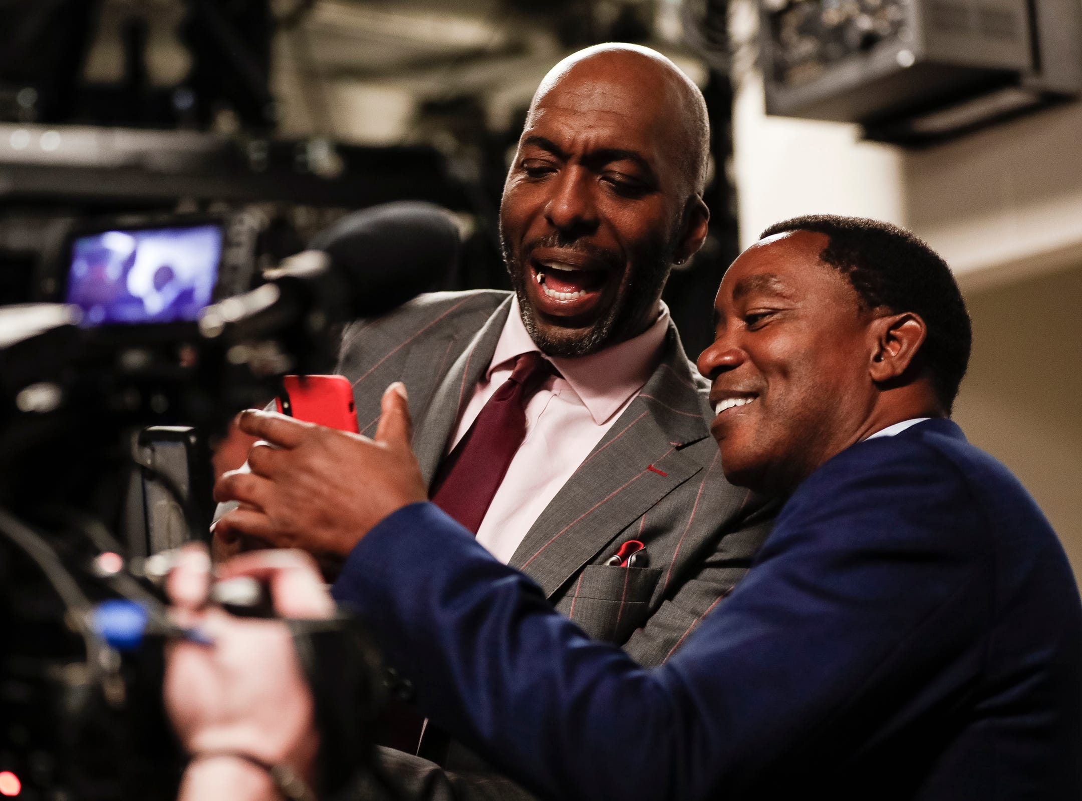 Isiah Thomas and John Salley try to set up live video on a phone before they walked out of the tunnel for the 30th anniversary of the 1989-90 back-to-back championships at the Little Caesars Arena in Detroit, Saturday, March 30, 2019.
