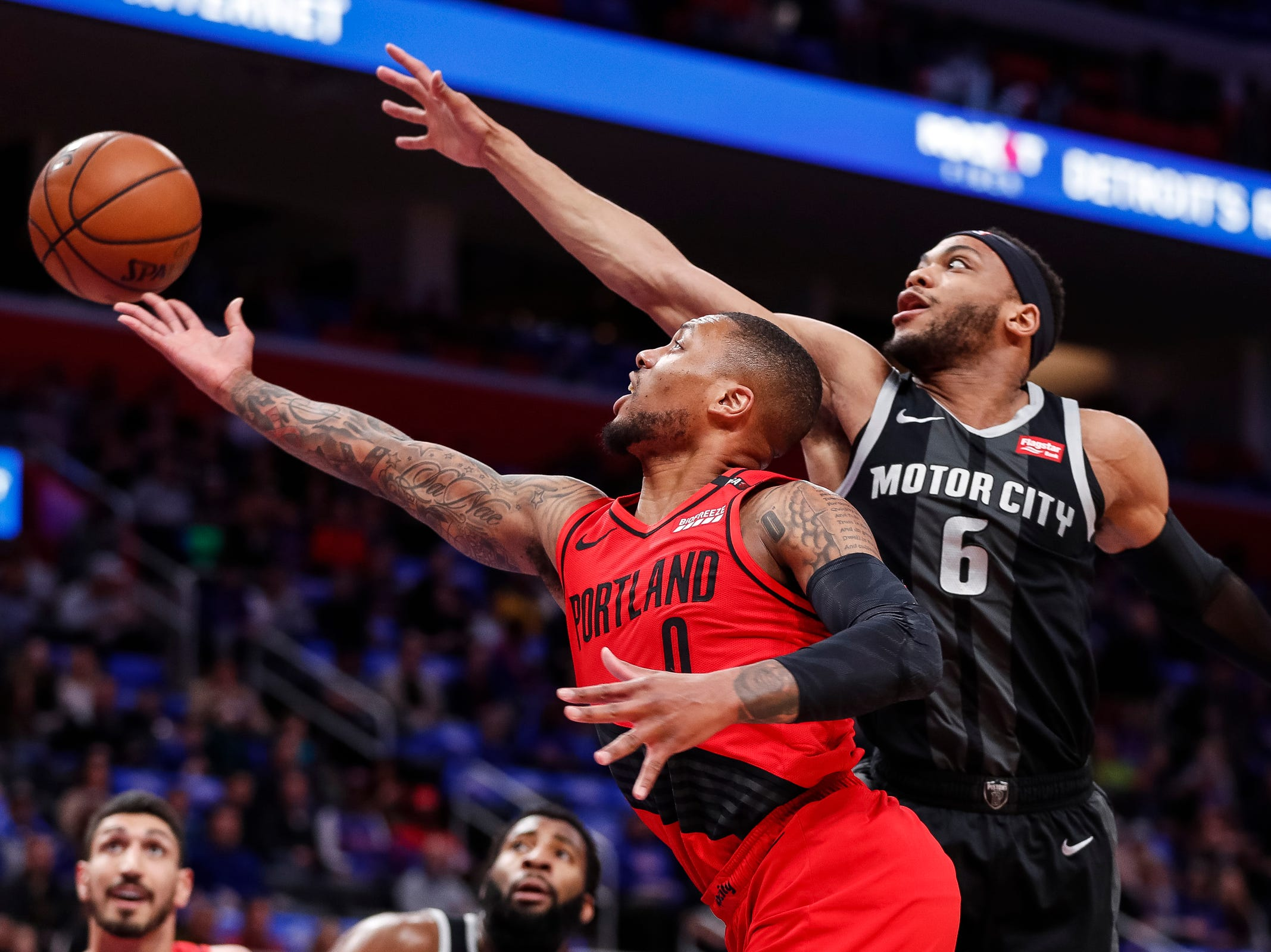 Trail Blazers guard Damian Lillard (0) makes a layup against Pistons guard Bruce Brown (6) during the first half at the Little Caesars Arena in Detroit, Saturday, March 30, 2019.