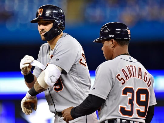 Tigers right fielder Nicholas Castellanos, left, stands on first base after hitting an RBI-single during the Tigers' 4-3 win in Toronto, Sunday, March 31, 2019.