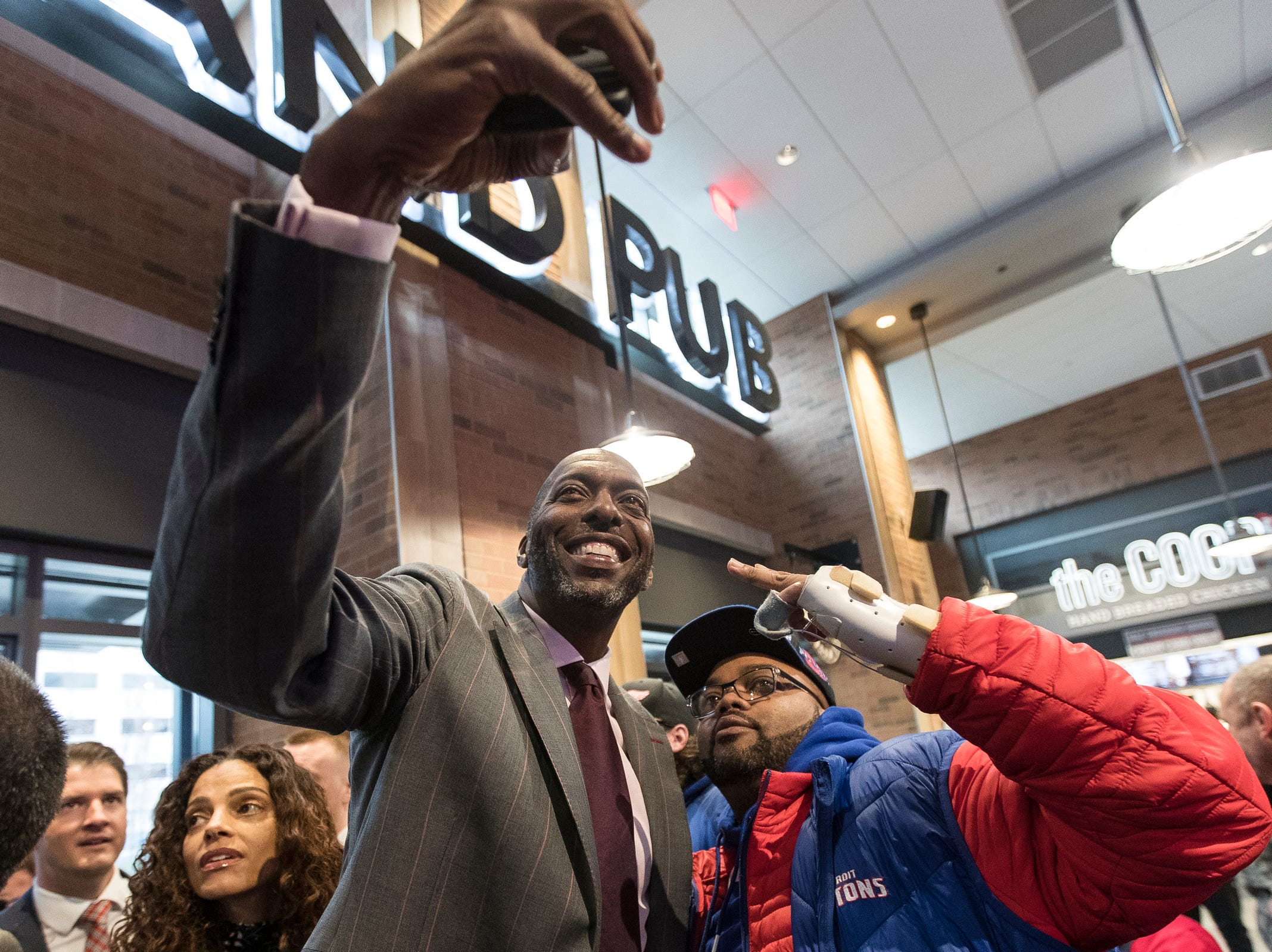 John Salley takes a selfie with a Pistons fan before the Pistons-Trail Blazers game at the Little Caesars Arena in Detroit, Saturday, March 30, 2019.