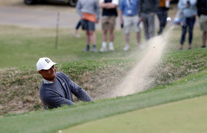 Tiger Woods plays a shot from a bunker on the 18th hole Saturday.