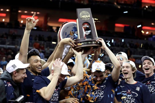 Members of Virginia celebrate after defeating Purdue 80-75 in overtime of the men's NCAA Tournament college basketball South Regional final game.