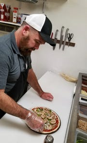 Owner Larry Hay Jr. assembles a pizza at Carolyn's Country Pizza-ria.