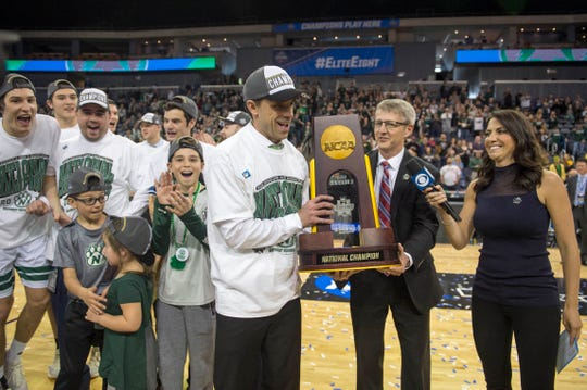 Jon Mark Hall hands off the 2019 NCAA Division II Men's Basketball National Championship trophy to Northwest Missouri State Head Coach Ben McCollum at Ford Center in Evansville, Ind., Saturday, March 30, 2019.   The Northwest Missouri State Bearcats defeated the Point Loma Sea Lions, 64-58.