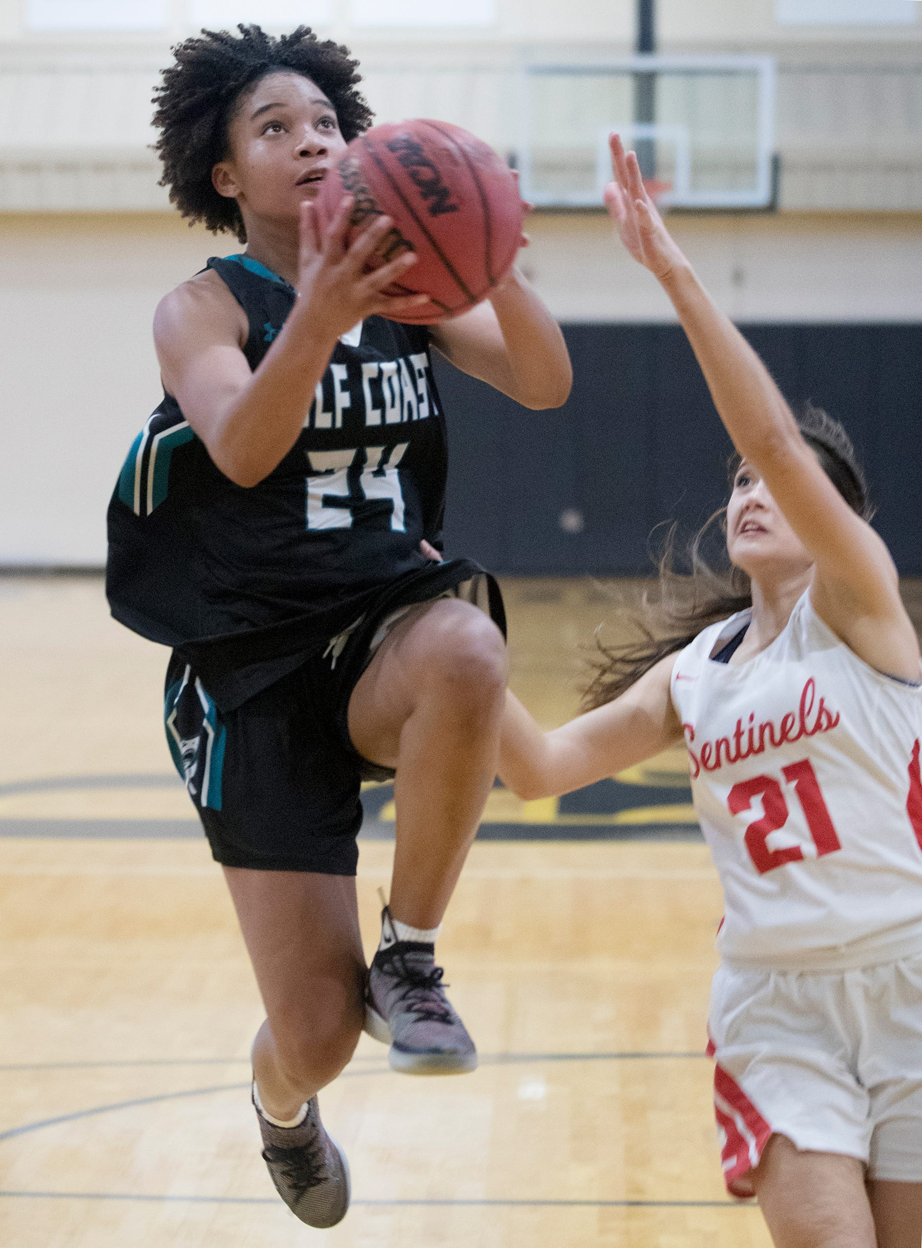 Gulf Coast High School's Yasmeen Chang, left, is defended by Evangelical Christian's Elizabeth Wetmore on Sunday during the SFABC Girls All-Star Basketball Game at Bishop Verot in Fort Myers.