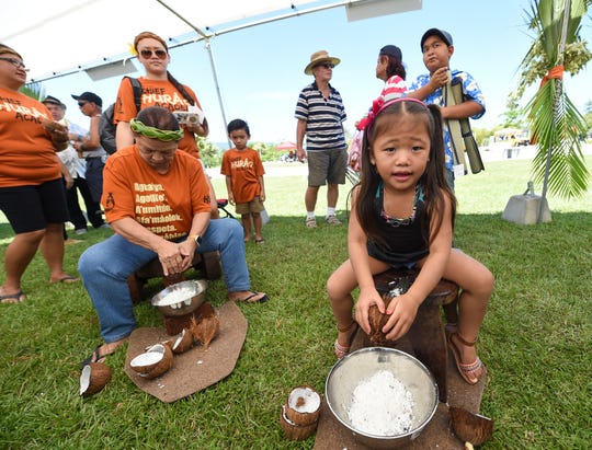 Charlie Jae Mendiola, 3, participates in a coconut grating demonstration during a Mes CHamoru celebration at Guam Windward Memorial in Yona, March 30, 2019.