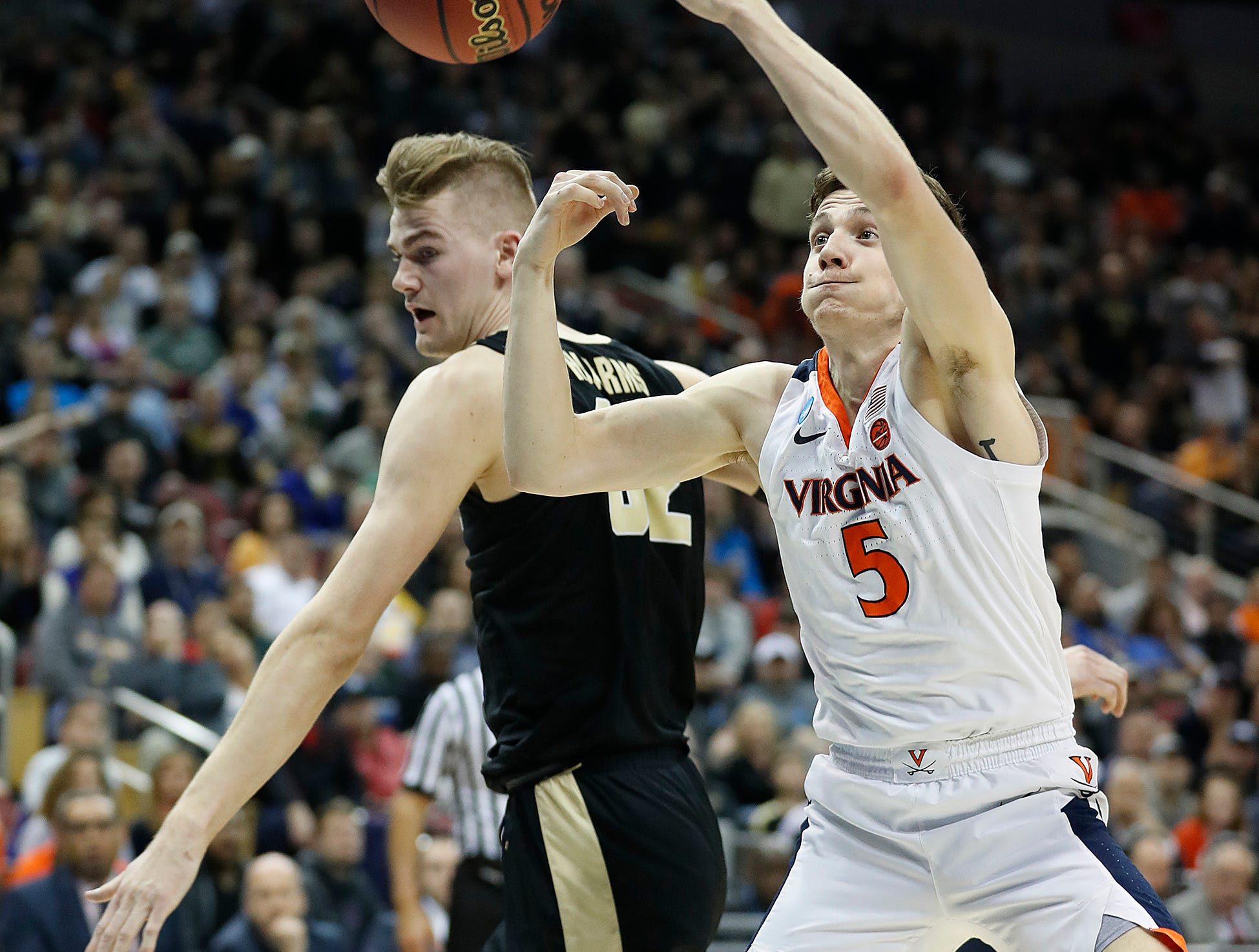 "Virginia Cavaliers guard Kyle Guy (5) and Purdue Boilermakers center Matt Haarms (32) fight for a rebound in the first half of their NCAA Division I Basketball Championship ""Elite 8"" basketball game at the KFC Yum! Center in Louisville, KY., on Saturday, Mar 30, 2019."
