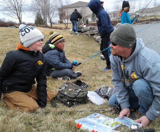 Rob Boaz of West Branch (right) talks tackle with his grinning son Robby, 10, while a friend, Jaimy Sanchez, fishes nearby at Saturday's North Liberty event.