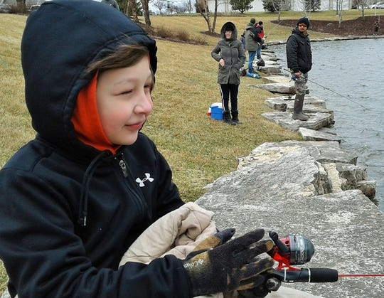 Kaden Casper, 9, of Tiffin donned gloves and was wrapped in a blanket, but still wore a smile fishing for trout Saturday.