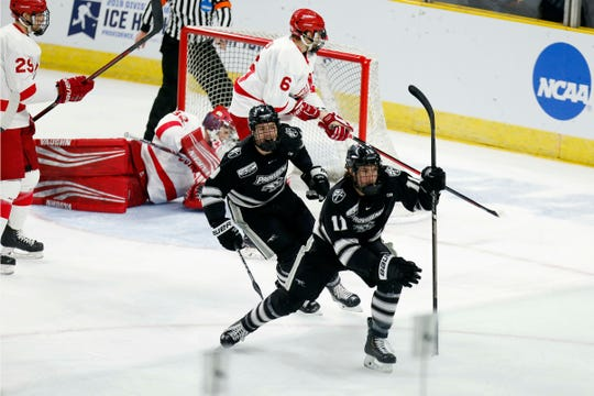 Providence's Greg Printz (11) celebrates his goal on Cornell's Austin McGrath (32) with teammate Brandon Duhaime (9) during the first period of the NCAA Division I East Regional final men's hockey game in Providence, R.I., Sunday, March 31, 2019. (AP Photo/Michael Dwyer)