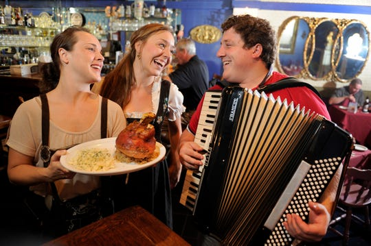 Former Restaurant Linderhof owner Aaron Schmissrauter, right, plays his accordion while joking with his servers Alanna Fletcher, left, and Emily McDaniel Thursday, Oct. 25, 2012.
