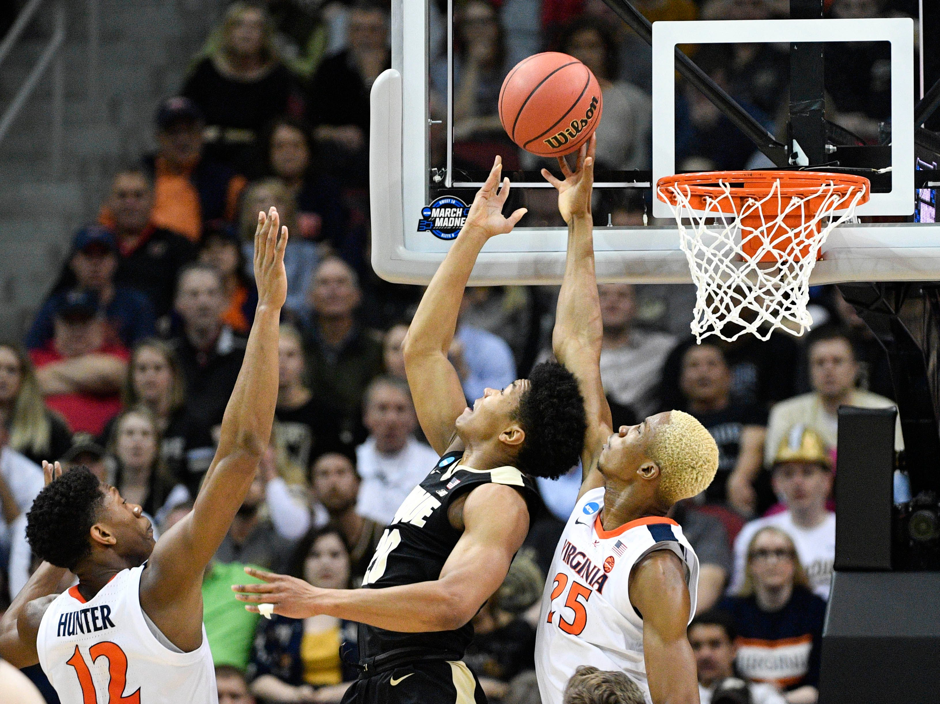 Mar 30, 2019; Louisville, KY, United States; Purdue Boilermakers guard Nojel Eastern (20) is defended by Virginia Cavaliers forward Mamadi Diakite (25) and guard De'Andre Hunter (12) during the first half in the championship game of the south regional of the 2019 NCAA Tournament at KFC Yum Center. Mandatory Credit: Jamie Rhodes-USA TODAY Sports