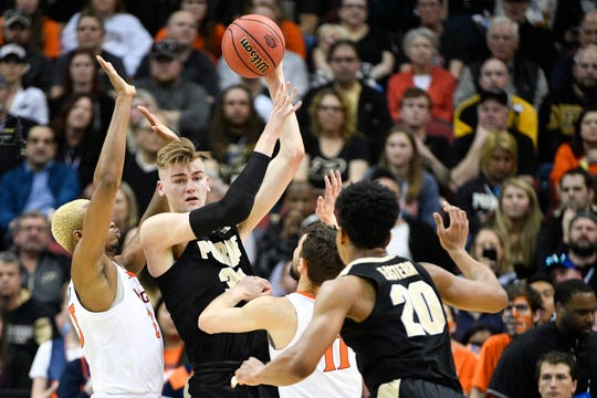 Boilermakers center Matt Haarms (32) looks to pass to guard Nojel Eastern (20) as Virginia Cavaliers guard Ty Jerome (11) and forward Mamadi Diakite (25) defend during the first half in the championship game of the south regional of the 2019 NCAA Tournament at KFC Yum Center.