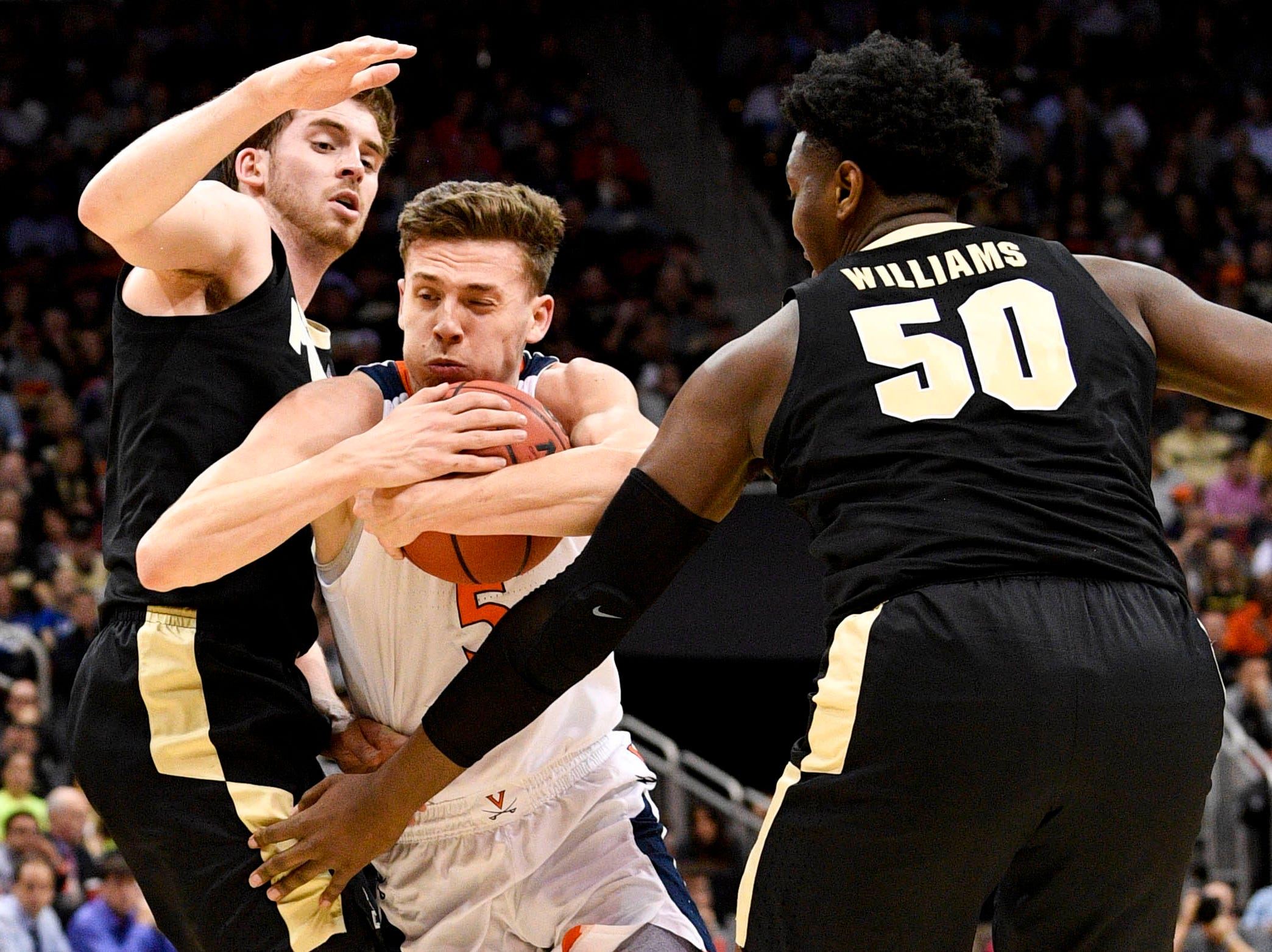 Mar 30, 2019; Louisville, KY, United States; Virginia Cavaliers guard Kyle Guy (5) drives through the defense of Purdue Boilermakers guard Ryan Cline (14) and forward Trevion Williams (50) during the first half in the championship game of the south regional of the 2019 NCAA Tournament at KFC Yum Center. Mandatory Credit: Jamie Rhodes-USA TODAY Sports