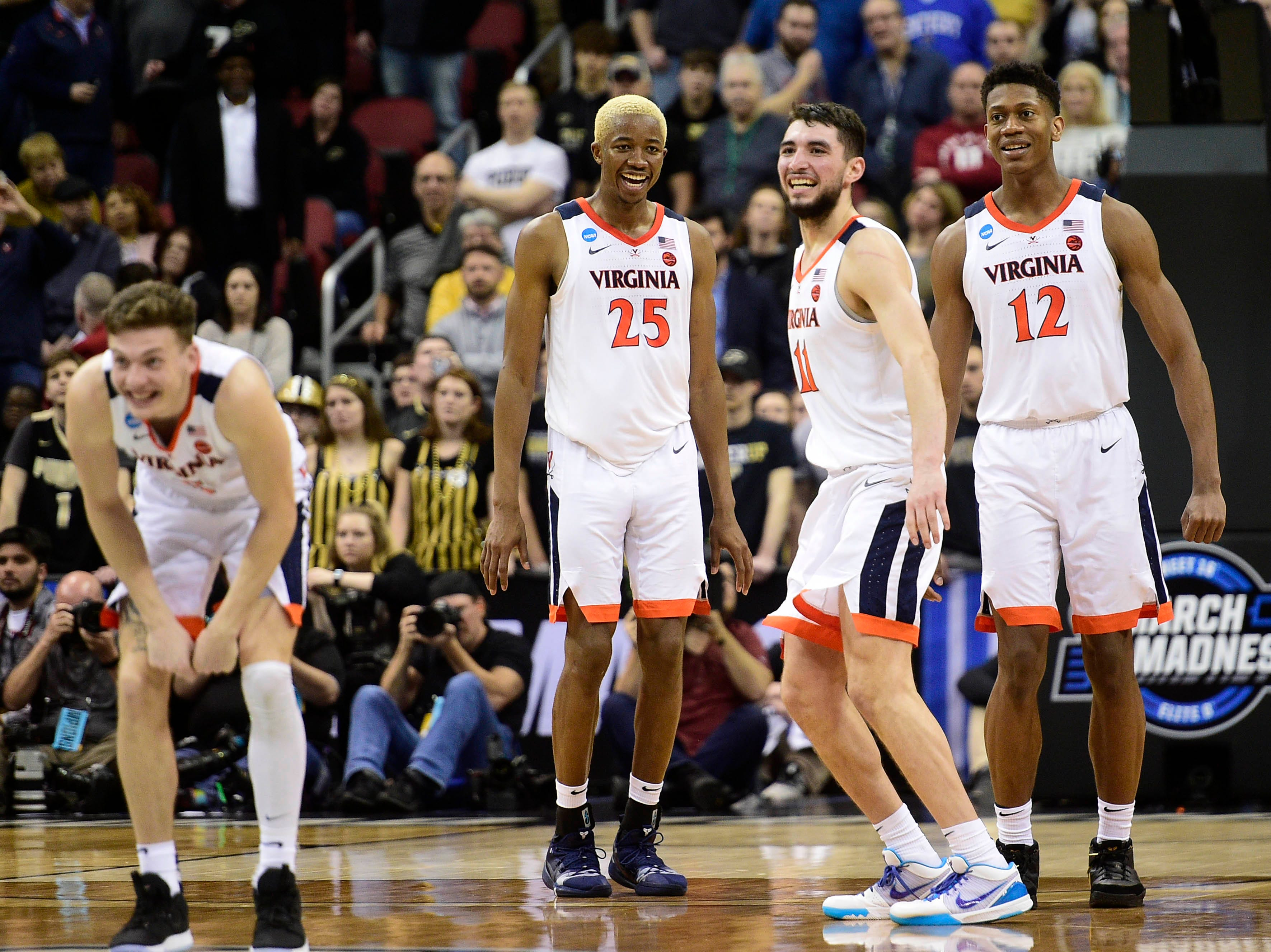 Mar 30, 2019; Louisville, KY, United States; Virginia Cavaliers guard Ty Jerome (11) celebrates with forward Mamadi Diakite (25) and guard De'Andre Hunter (12) after the win over the Purdue Boilermakers in overtime in the championship game of the south regional of the 2019 NCAA Tournament at KFC Yum Center. Mandatory Credit: Thomas J. Russo-USA TODAY Sports