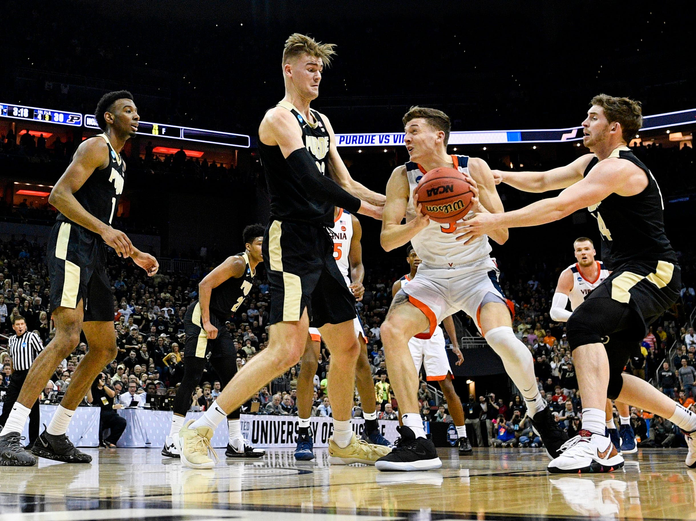 Mar 30, 2019; Louisville, KY, United States; Virginia Cavaliers guard Kyle Guy (5) holds the ball as Purdue Boilermakers center Matt Haarms (32) and guard Ryan Cline (14) defend during the first half in the championship game of the south regional of the 2019 NCAA Tournament at KFC Yum Center. Mandatory Credit: Jamie Rhodes-USA TODAY Sports
