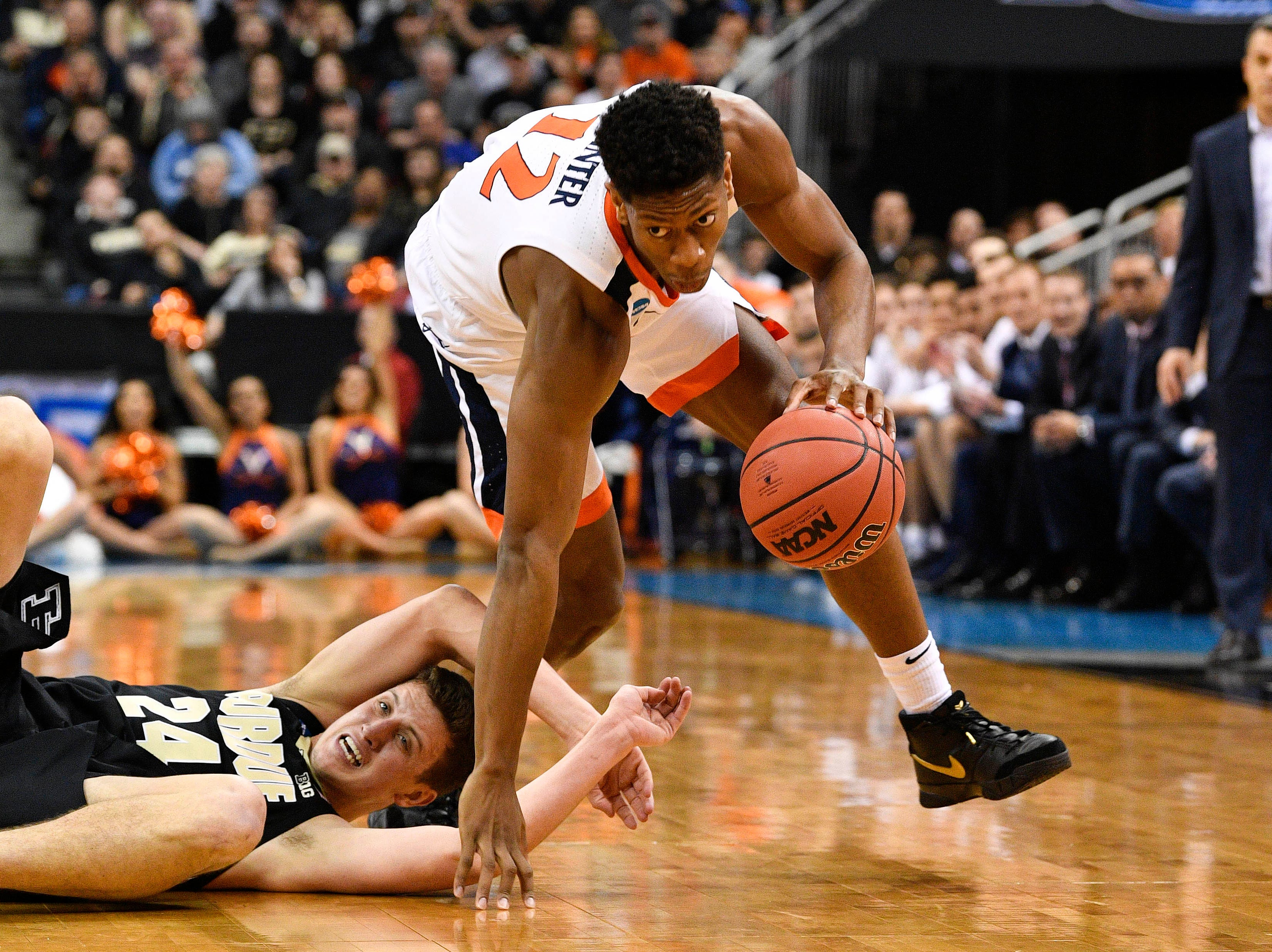Mar 30, 2019; Louisville, KY, United States; Virginia Cavaliers guard De'Andre Hunter (12) dribbles over Purdue Boilermakers forward Grady Eifert (24) during the first half in the championship game of the south regional of the 2019 NCAA Tournament at KFC Yum Center. Mandatory Credit: Jamie Rhodes-USA TODAY Sports