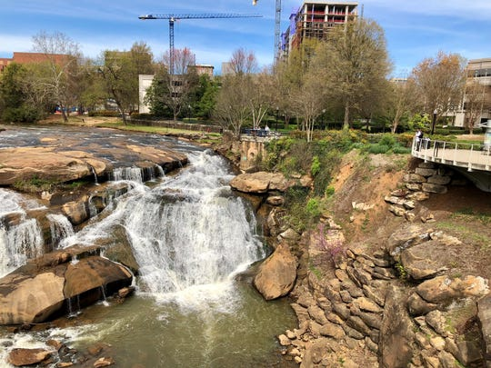 The Reedy River runs through downtown Greenville, South Carolina. A pedestrian bridge overlooks the falls. One Acadiana organized a three-day trip to Greenville.