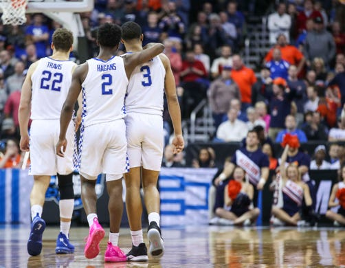 Kentucky's Reid Travis, left, walks as Ashton Hagans puts an arm around Keldon Johnson as their loss becomes clear as Wildcats fell to Auburn 77-71 Sunday afternoon in the Elite Eight. March 31, 2019