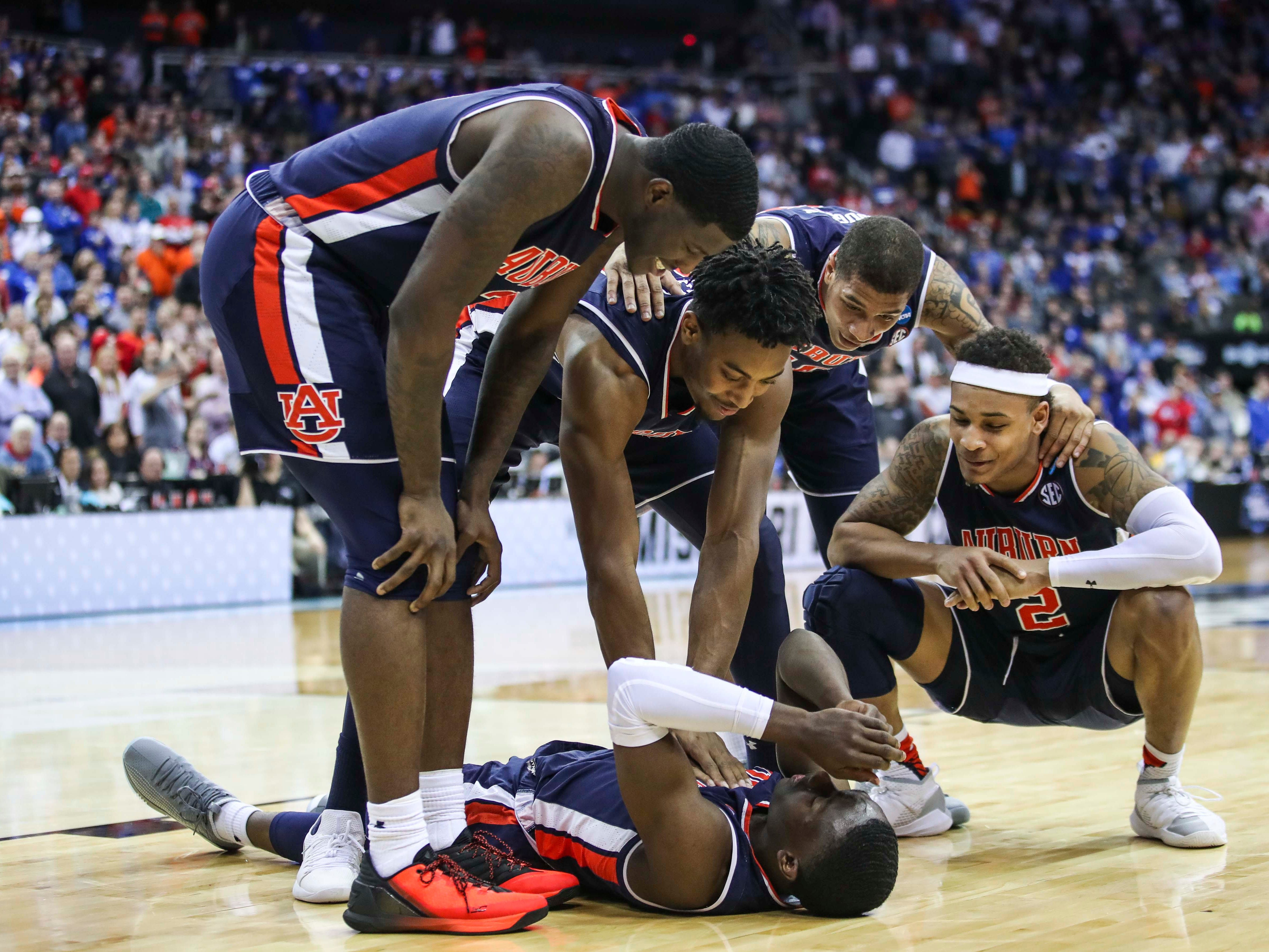 Auburn players surround teammate Jared Harper in the waning second as Wildcats fell to Auburn 77-71 Sunday afternoon in the Elite Eight. March 31, 2019