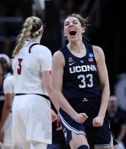 UConn's Katie Lou Samuelson (33) screamed after hitting a 3-point shot and getting fouled by U of L's Sam Fuehring (3) during their Elite 8 matchup in Albany, N.Y.  UConn won 80-73. Mar. 31, 2019.