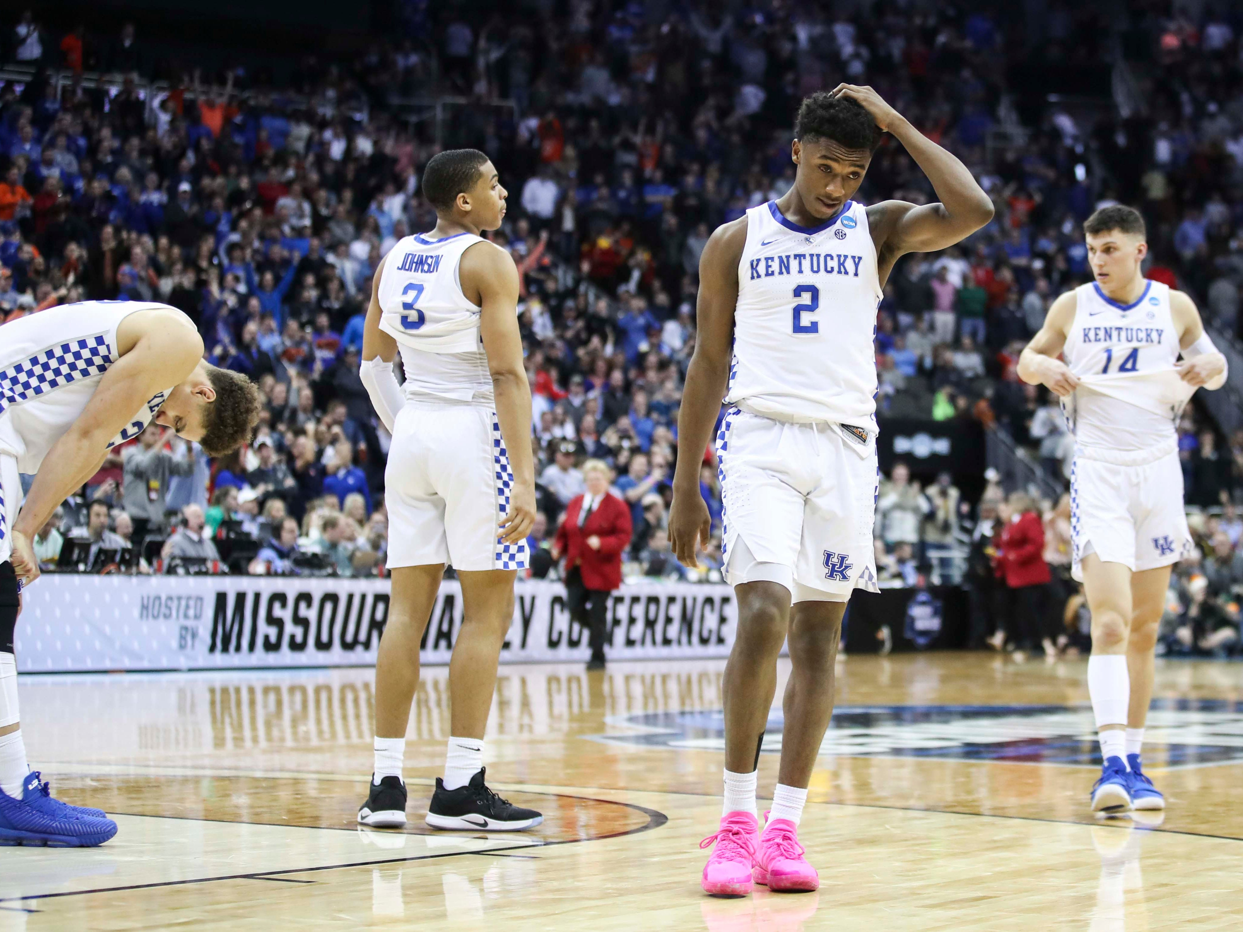 A stunned-looking Ashton Hagans (2) of Kentucky holds his head as Reid Travis, far left, Keldon Johnson and Tyler Herro stand disappointed after the Wildcats fell to Auburn Sunday afternoon in the Elite Eight. March 31, 2019