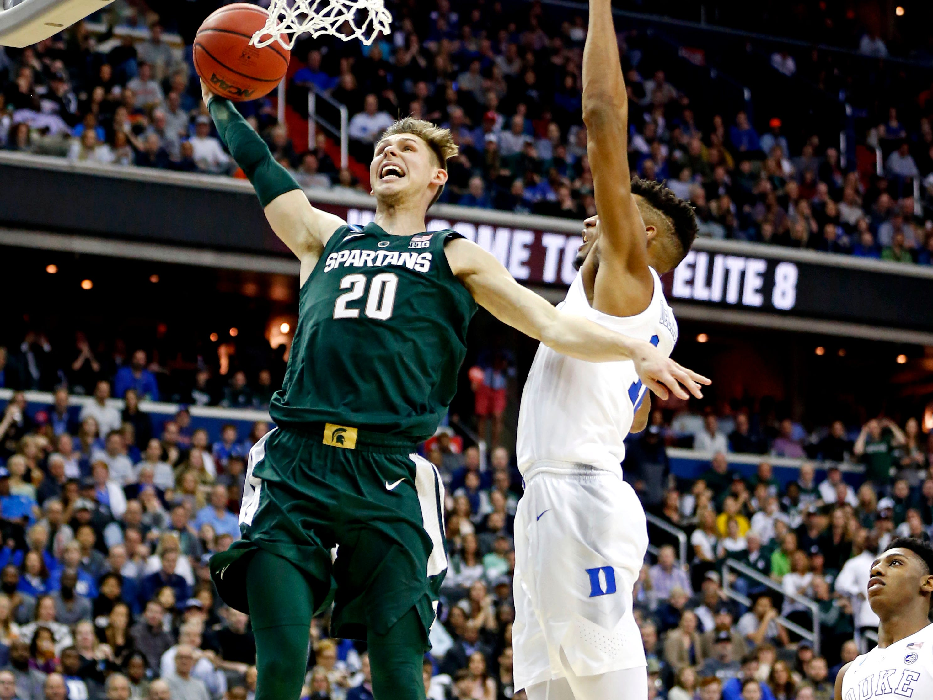 Michigan State Spartans guard Matt McQuaid (20) dunks the ball against Duke Blue Devils forward Javin DeLaurier (12) during the first half in the championship game of the east regional of the 2019 NCAA Tournament at Capital One Arena.