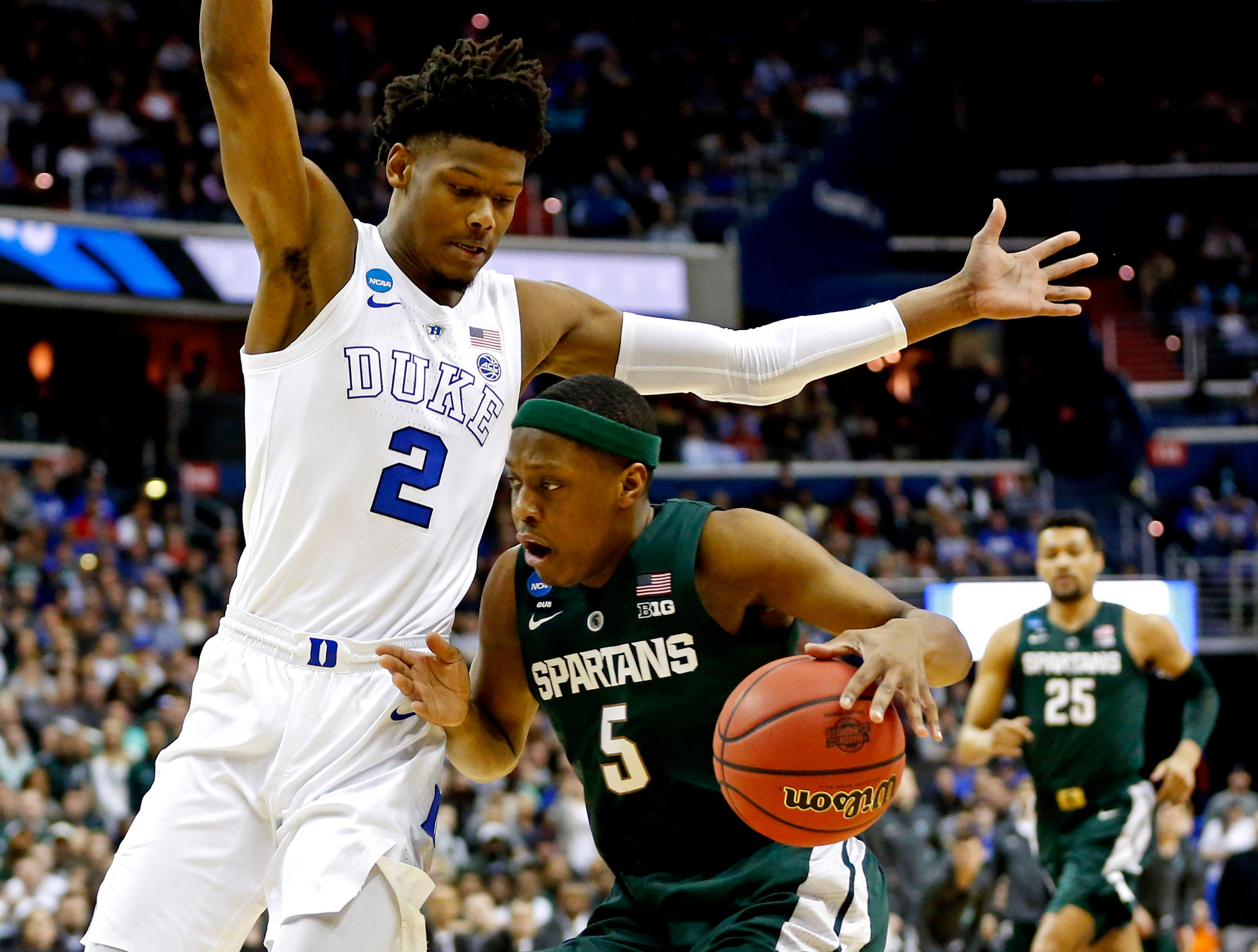 Michigan State Spartans guard Cassius Winston (5) drives to the basket against Duke Blue Devils forward Cam Reddish (2) during the first half in the championship game of the east regional of the 2019 NCAA Tournament at Capital One Arena.