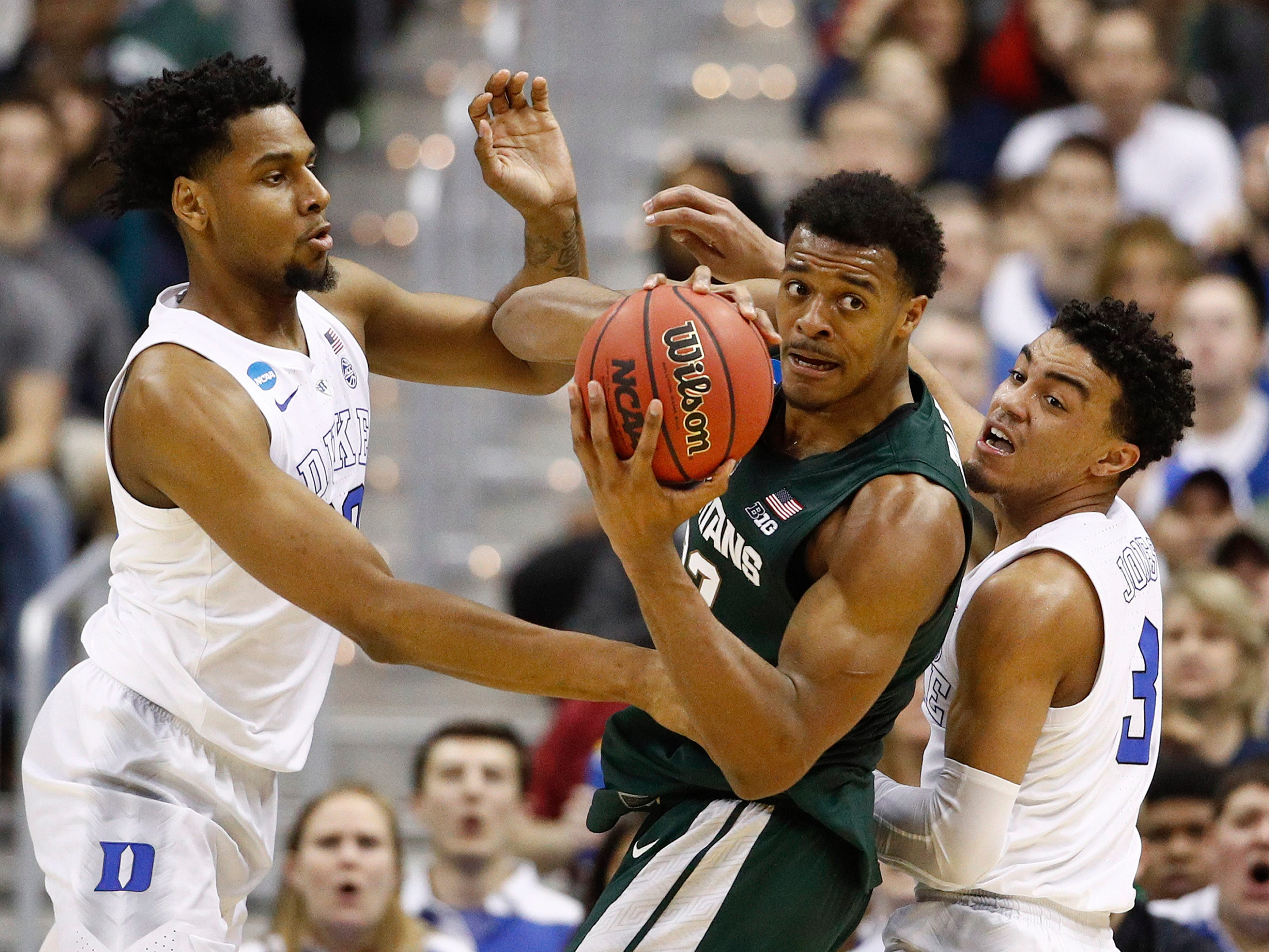 Michigan State forward Xavier Tillman (23) looks to pass the ball as he is covered by Duke center Marques Bolden (20) guard Tre Jones (3) during the first half of an NCAA men's East Regional final college basketball game in Washington, Sunday, March 31, 2019.