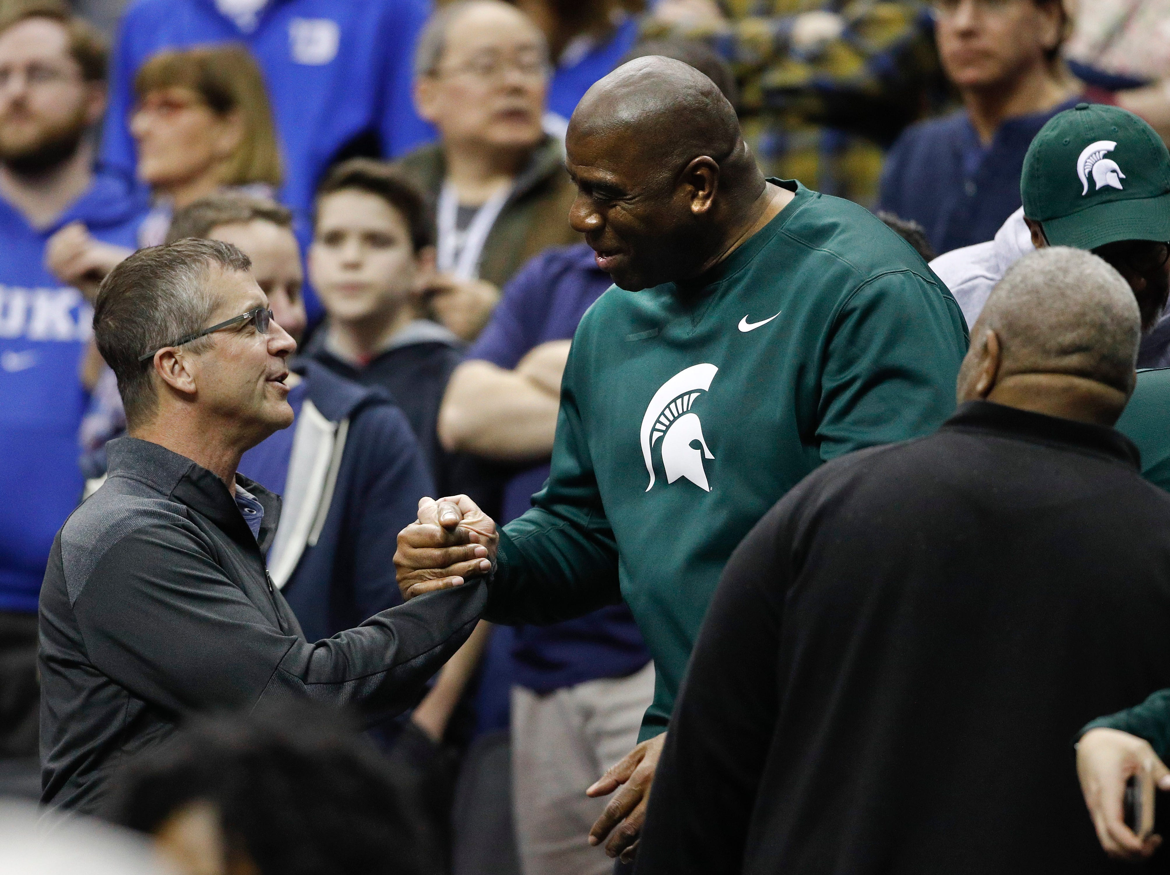 Los Angeles Lakers president and Michigan State alumni Magic Johnson, right, greets Baltimore Ravens head coach John Harbaugh, left, before the start of a NCAA men's East Regional final college basketball game between Michigan State and Duke in Washington, Sunday, March 31, 2019.