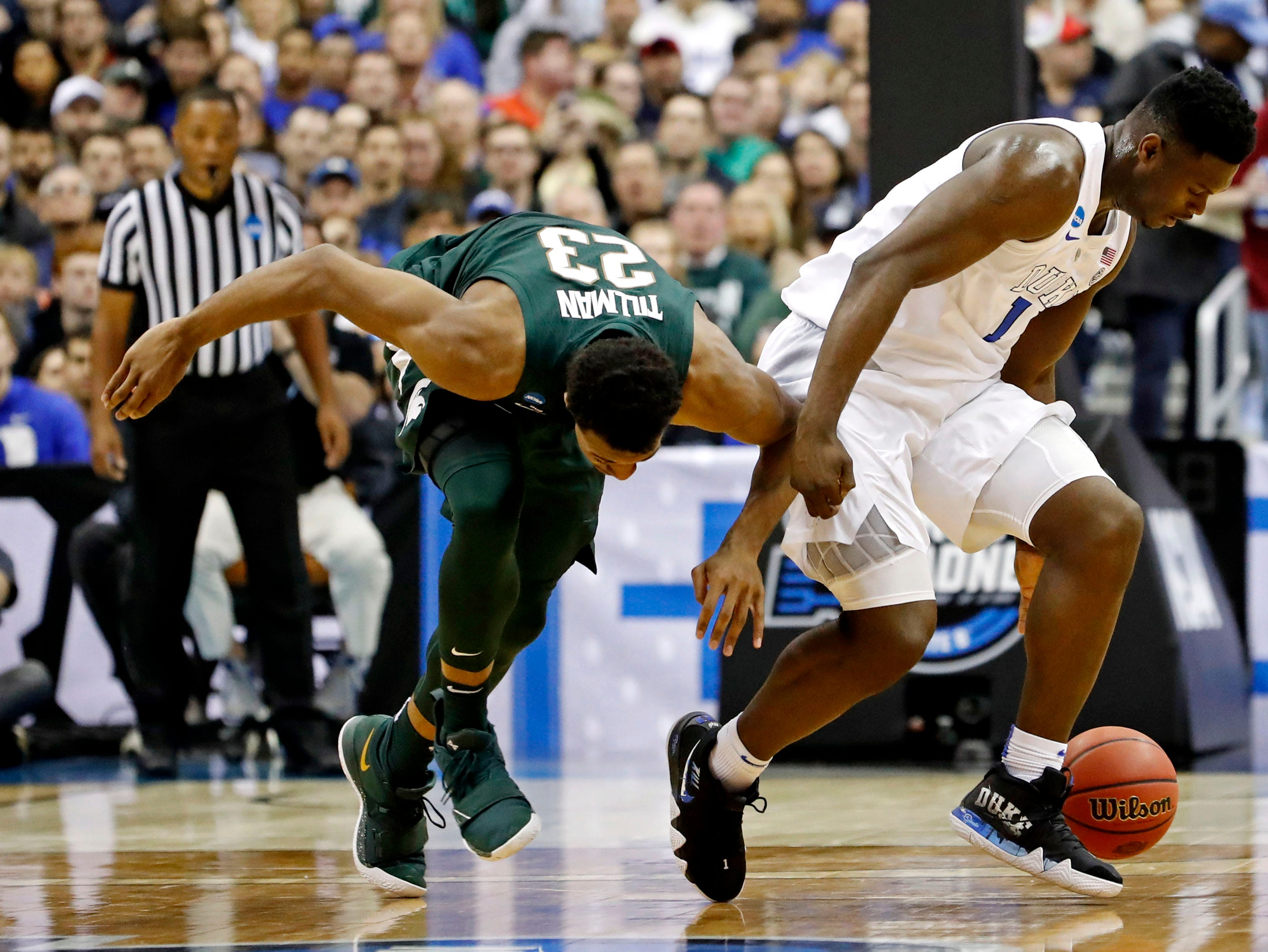 Mar 31, 2019; Washington, DC, USA; Duke Blue Devils forward Zion Williamson (1) and Michigan State Spartans forward Xavier Tillman (23) for a loose ball during the first half in the championship game of the east regional of the 2019 NCAA Tournament at Capital One Arena. Mandatory Credit: Geoff Burke-USA TODAY Sports