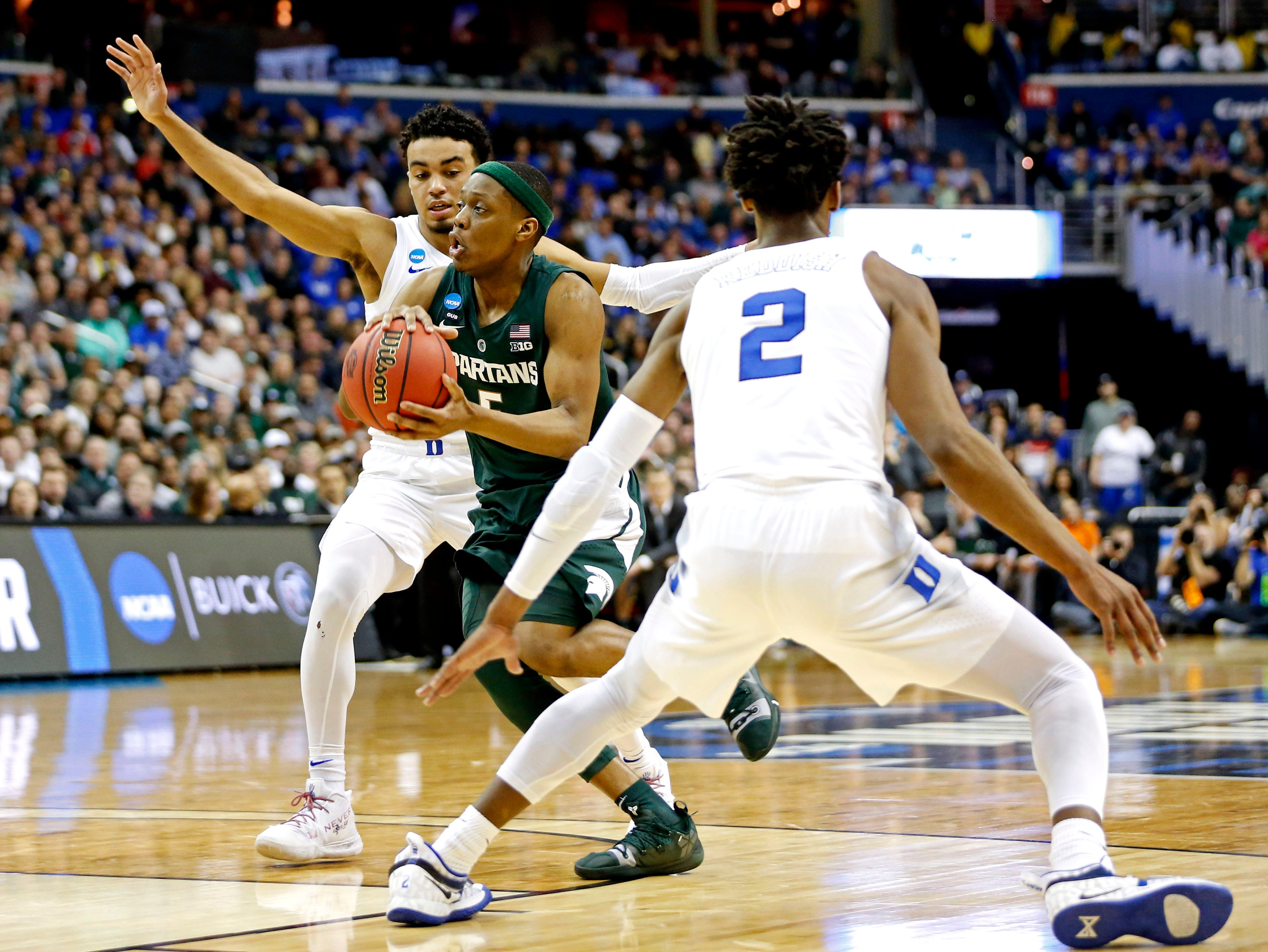 Mar 31, 2019; Washington, DC, USA; Michigan State Spartans guard Cassius Winston (5) drives to the basket against Duke Blue Devils forward Cam Reddish (2) and guard Tre Jones (3) during the first half in the championship game of the east regional of the 2019 NCAA Tournament at Capital One Arena. Mandatory Credit: Amber Searls-USA TODAY Sports