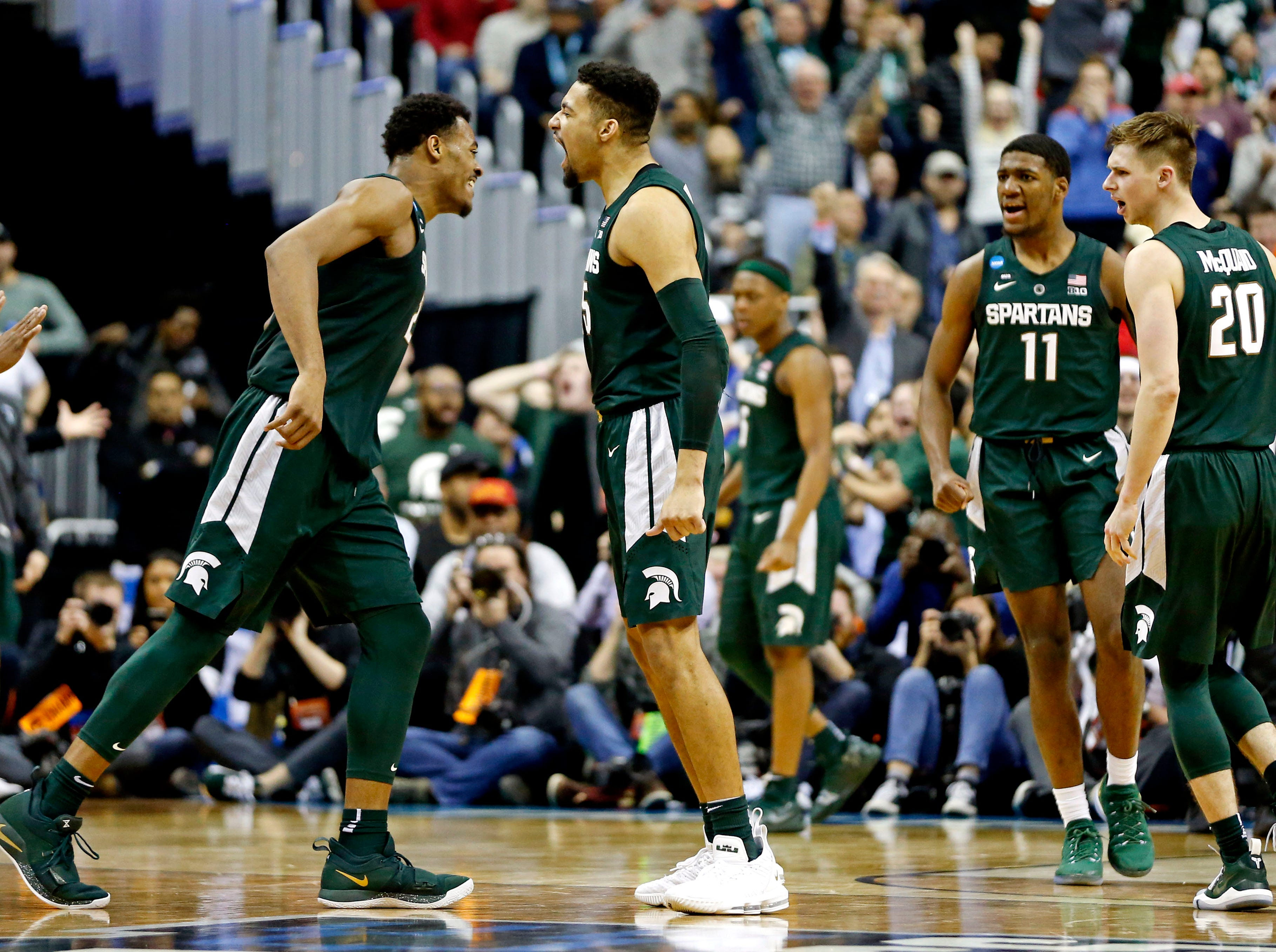 Mar 31, 2019; Washington, DC, USA; Michigan State Spartans forward Kenny Goins (25) celebrated with Michigan State Spartans forward Xavier Tillman (23) during the second half against the Duke Blue Devils in the championship game of the east regional of the 2019 NCAA Tournament at Capital One Arena. Mandatory Credit: Amber Searls-USA TODAY Sports