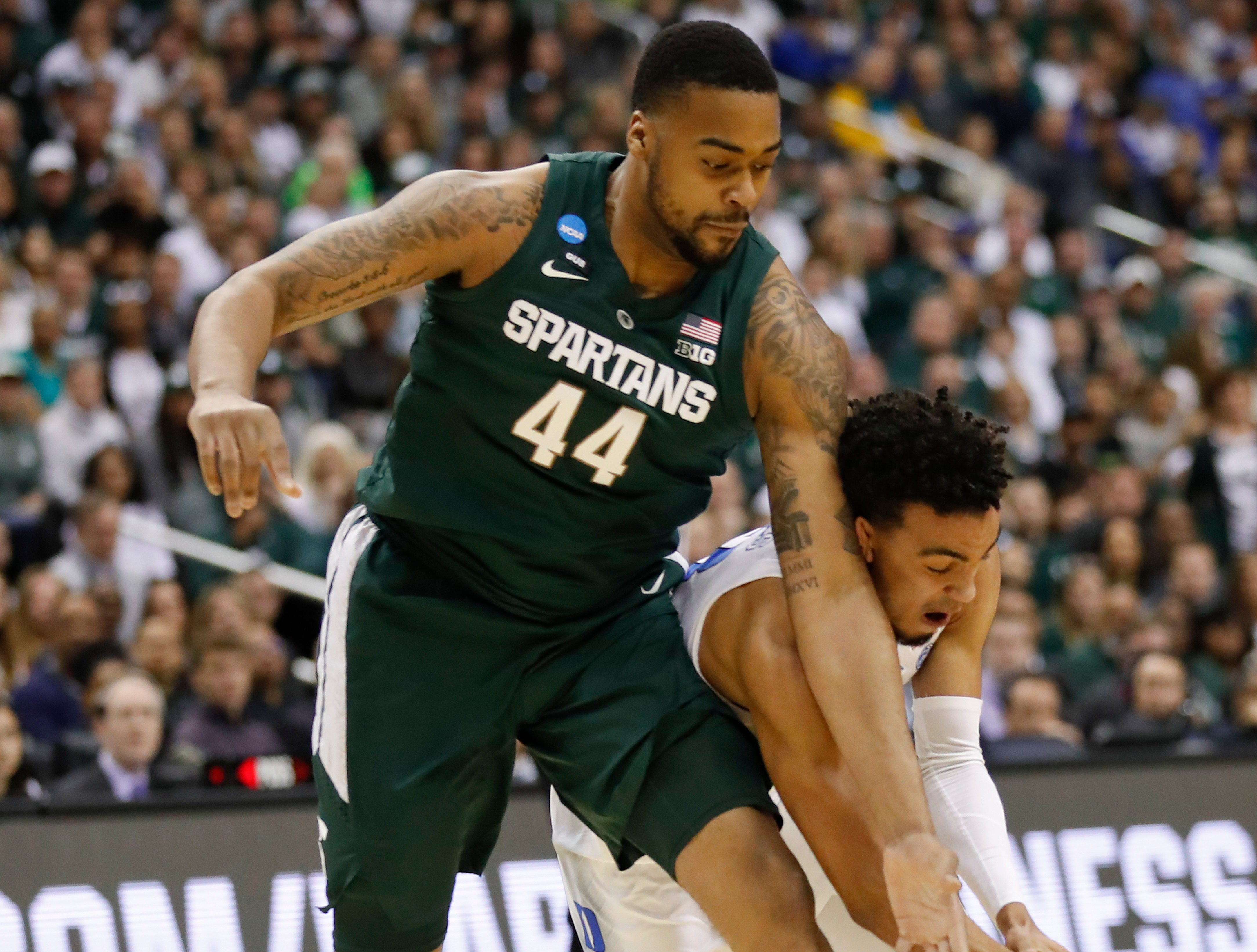 Duke guard Tre Jones (3) and Michigan State forward Nick Ward (44) fight for the ball during the first half of an NCAA men's East Regional final college basketball game in Washington, Sunday, March 31, 2019.