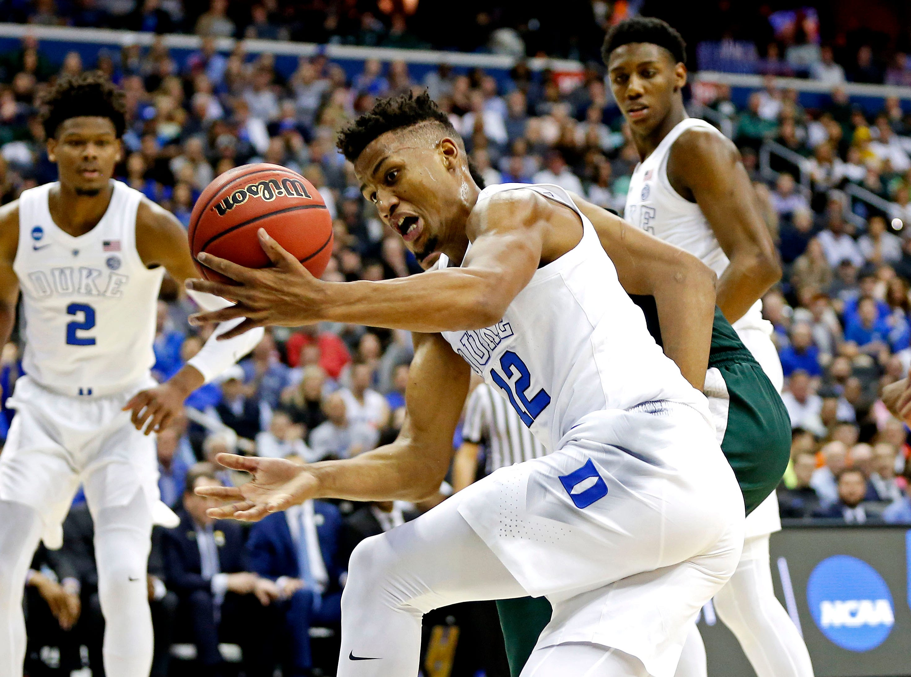 Mar 31, 2019; Washington, DC, USA; Duke Blue Devils forward Javin DeLaurier (12) goes for a loose ball against Michigan State Spartans forward Xavier Tillman (23) during the first half in the championship game of the east regional of the 2019 NCAA Tournament at Capital One Arena. Mandatory Credit: Amber Searls-USA TODAY Sports