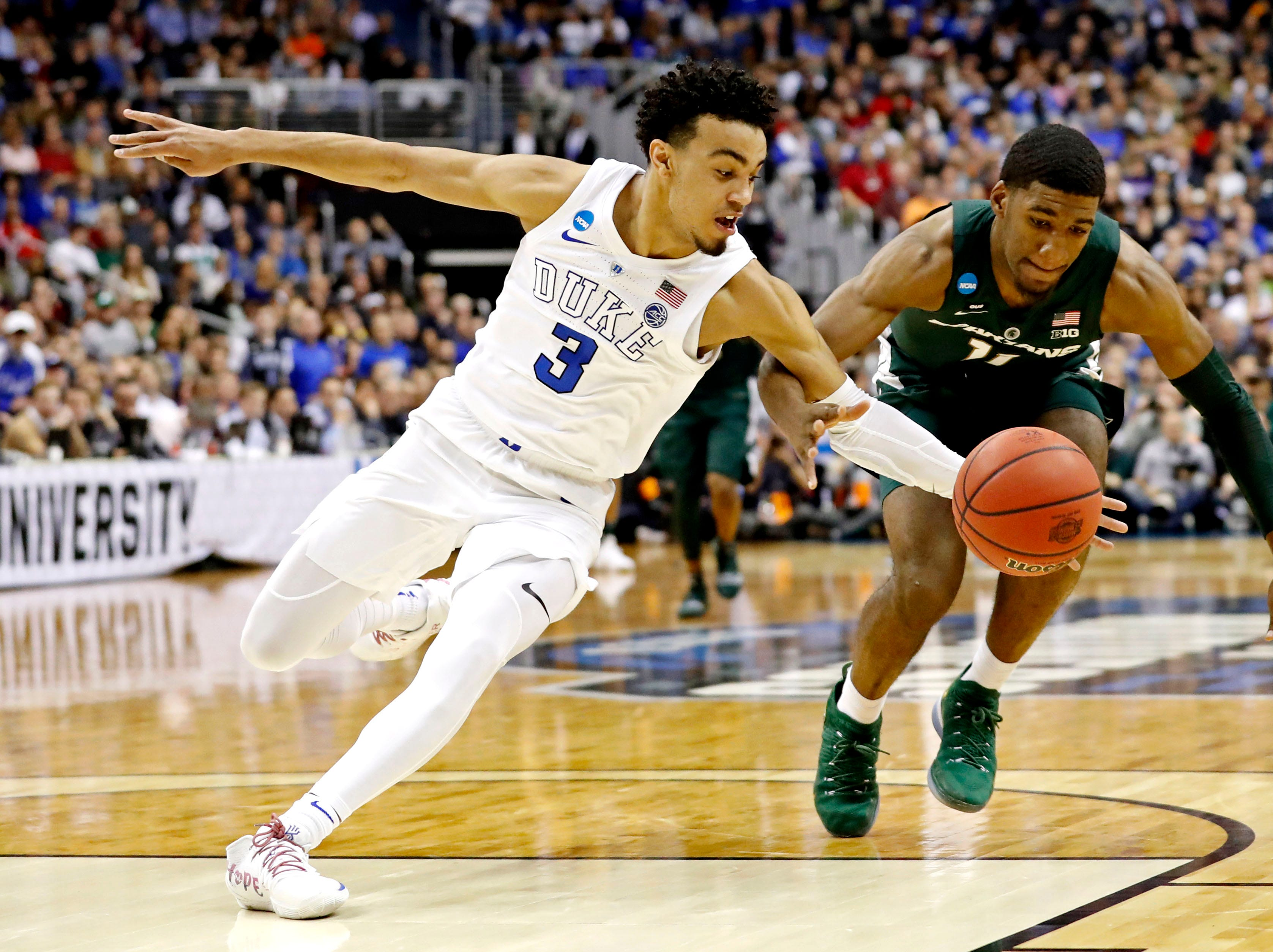 Duke Blue Devils guard Tre Jones (3) and Michigan State Spartans forward Aaron Henry (11) go for a loose ball during the first half in the championship game of the east regional of the 2019 NCAA Tournament at Capital One Arena.