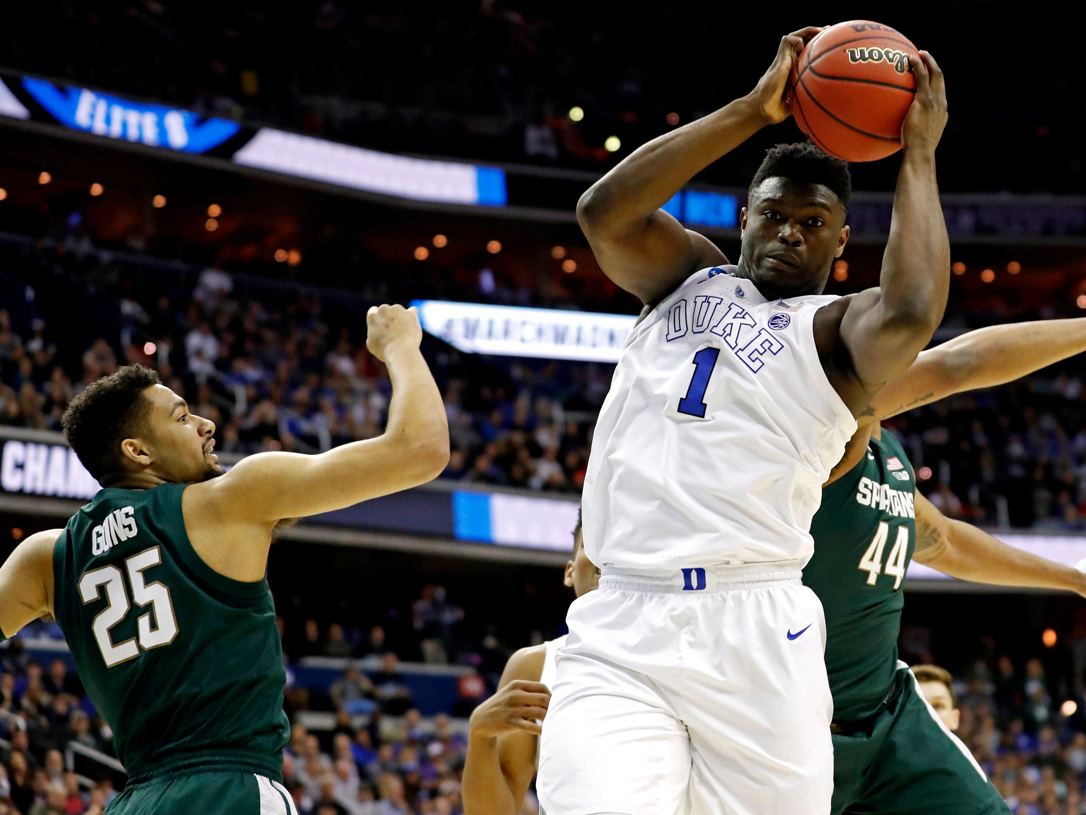Mar 31, 2019; Washington, DC, USA; Duke Blue Devils forward Zion Williamson (1) grabs a rebound against Michigan State Spartans forward Nick Ward (44) and forward Kenny Goins (25) during the first half in the championship game of the east regional of the 2019 NCAA Tournament at Capital One Arena. Mandatory Credit: Geoff Burke-USA TODAY Sports